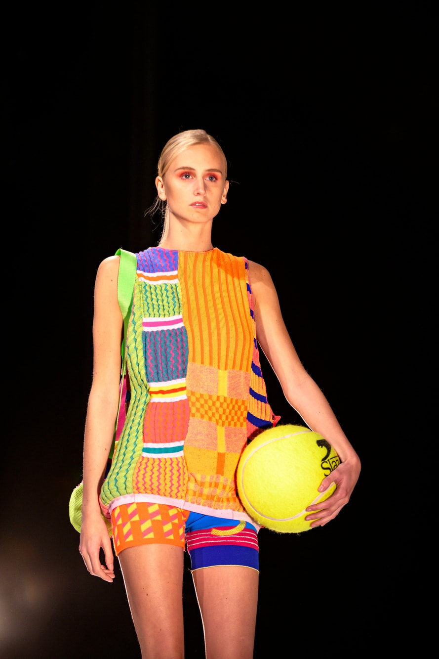 A female model holds an oversized tennis ball wearing a knitted brightly coloured vest and shorts