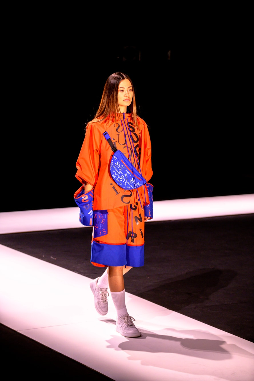 A female model in orange and blue waterproof oversized jacket and knee length shorts wears a blue bumbag over her shoulder