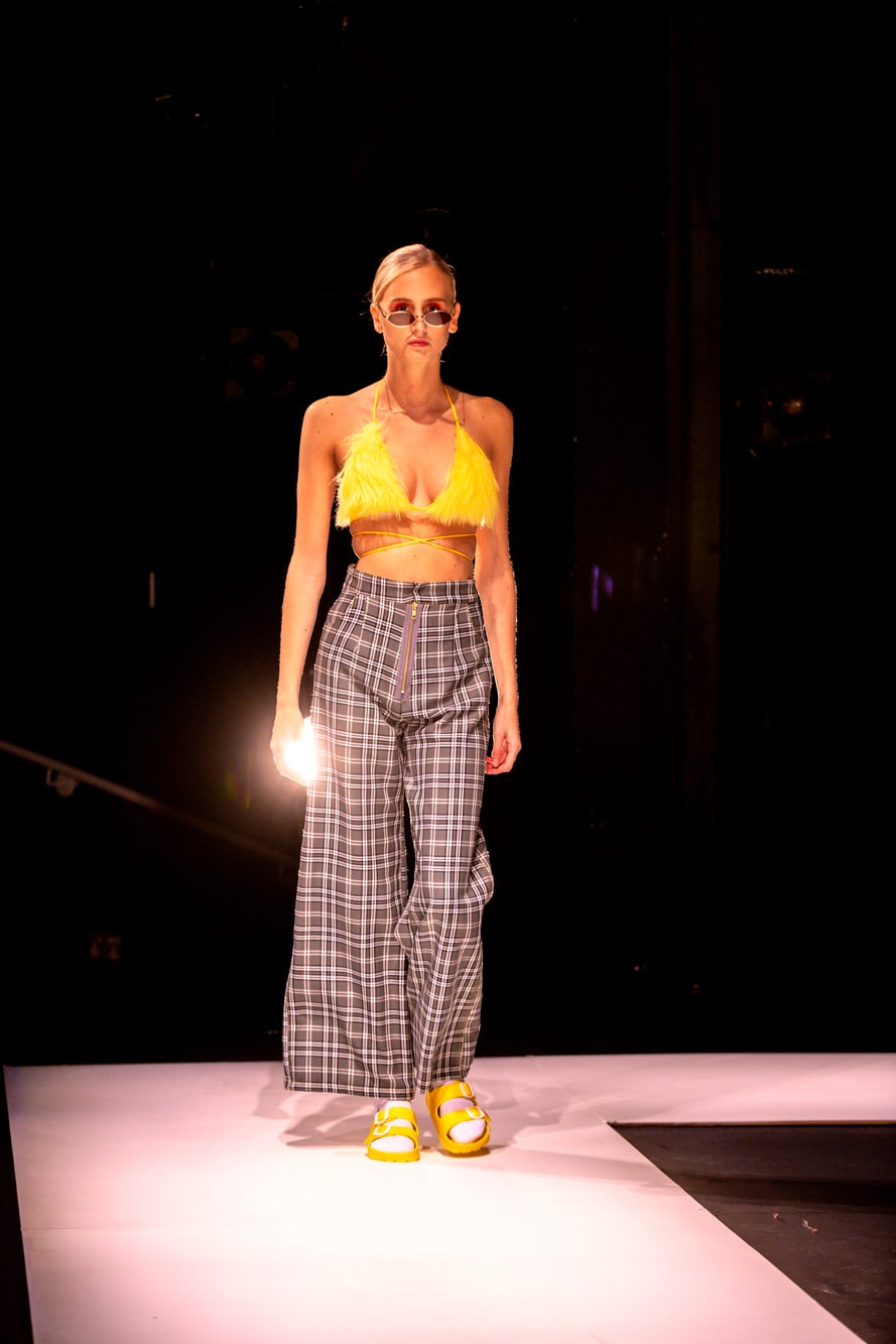 A female model wears sunglasses, a bright yellow bikini top and wide legged check trousers