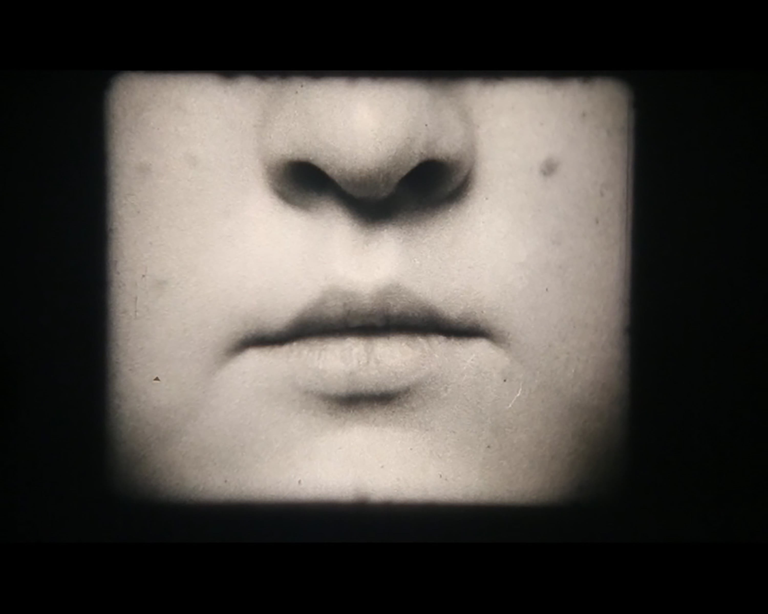 Black and white photo of a close up of someones nose and lips