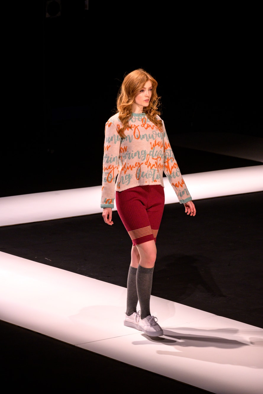 A female model walks the catwalk in a knitted top and knee length shorts