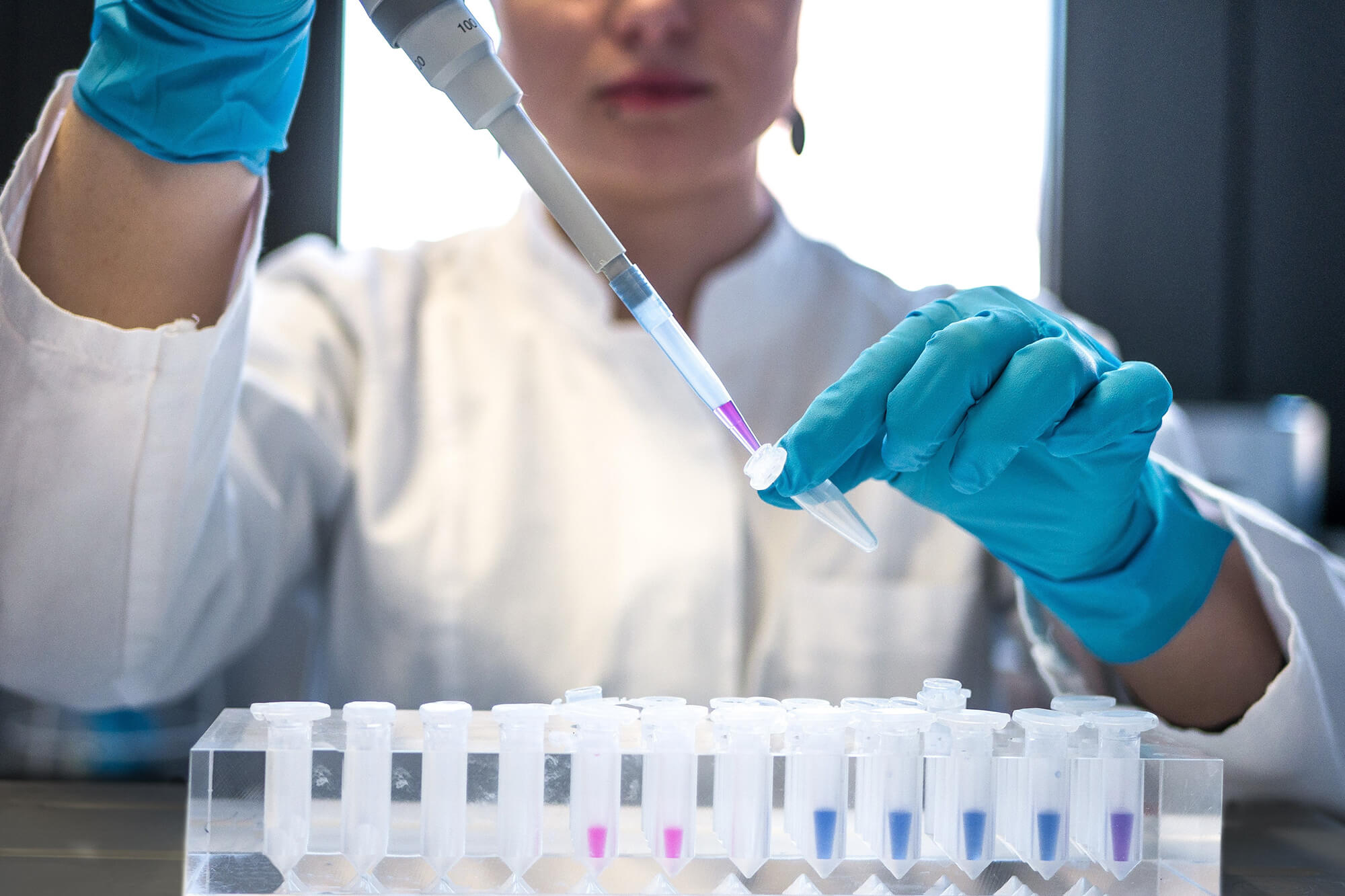 A researcher using a pipette to insert fluid into a tube