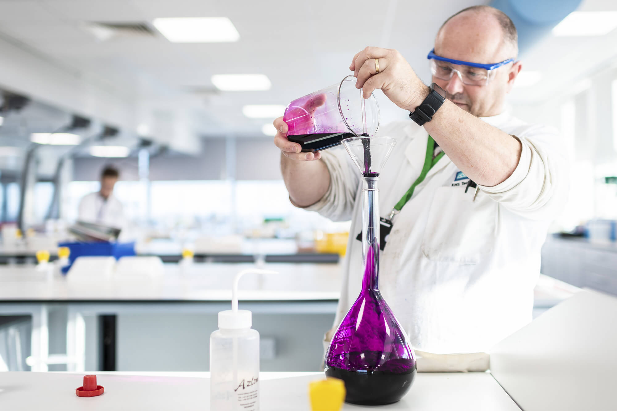An academic in a lab pouring purple liquid into a glass test tube.
