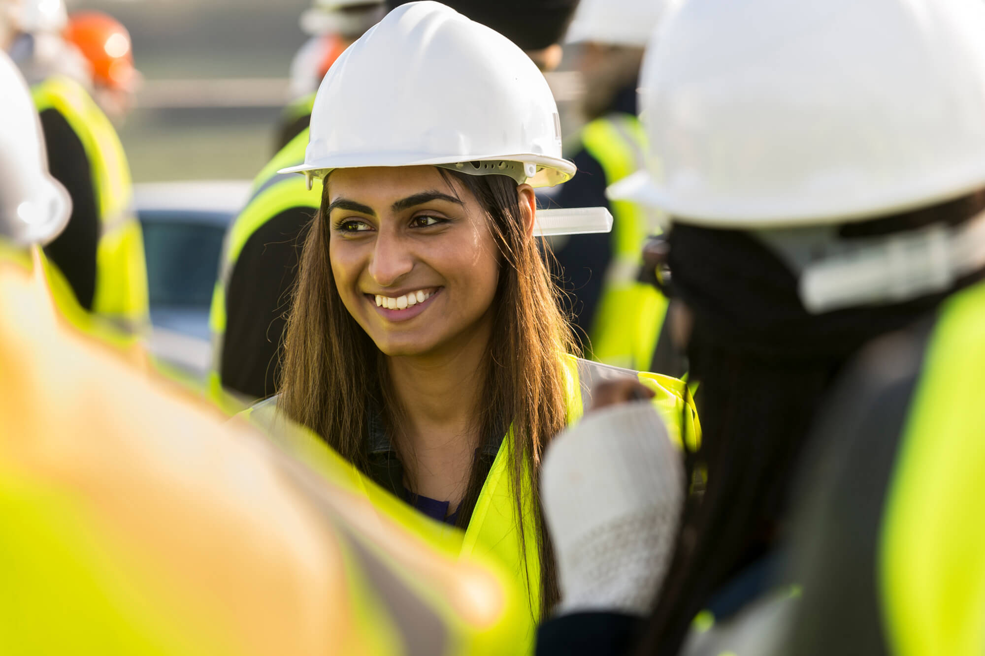 Female student on a building site with an high vis jacket and hard hat on smiling at the camera