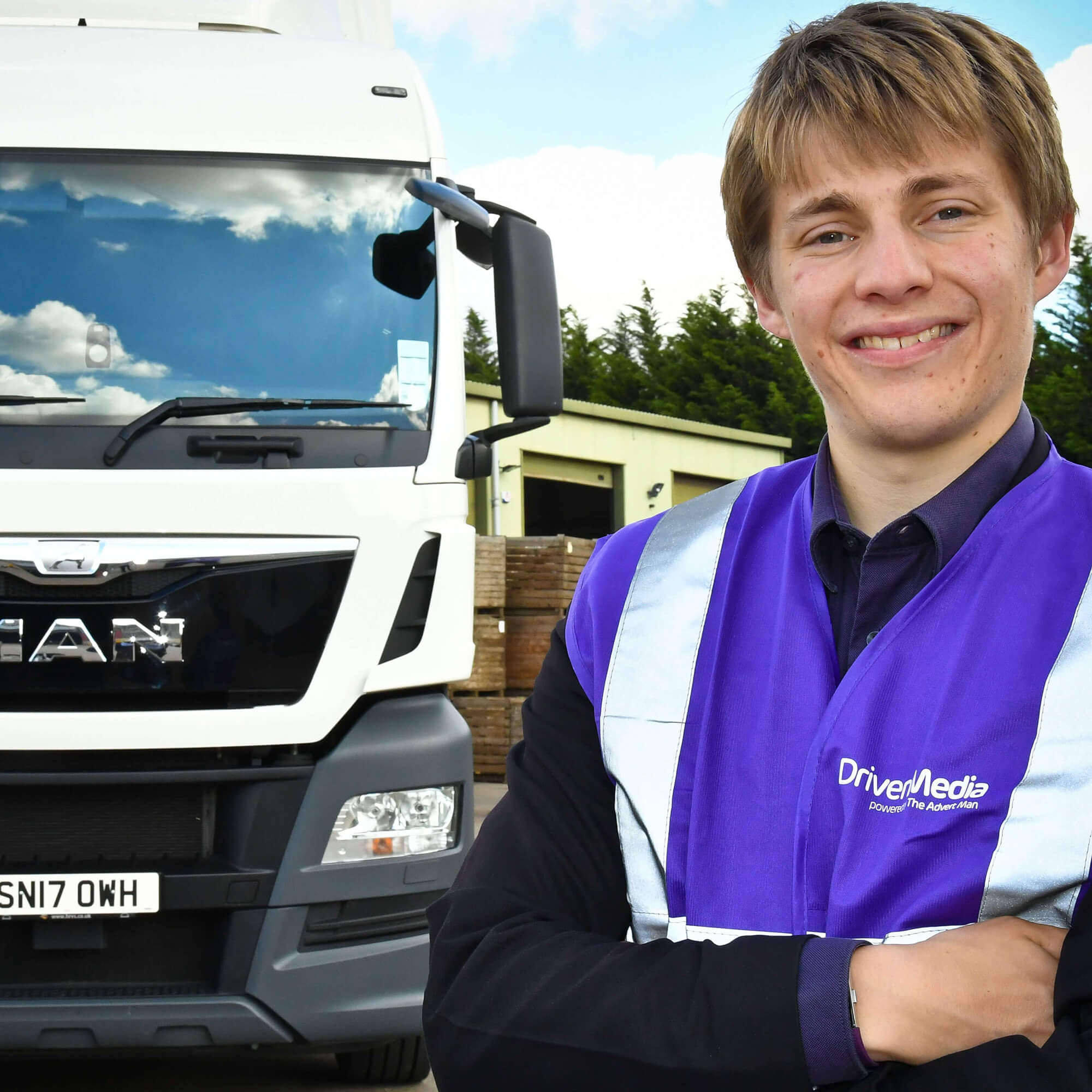 Ed standing next to a truck with arms crossed.