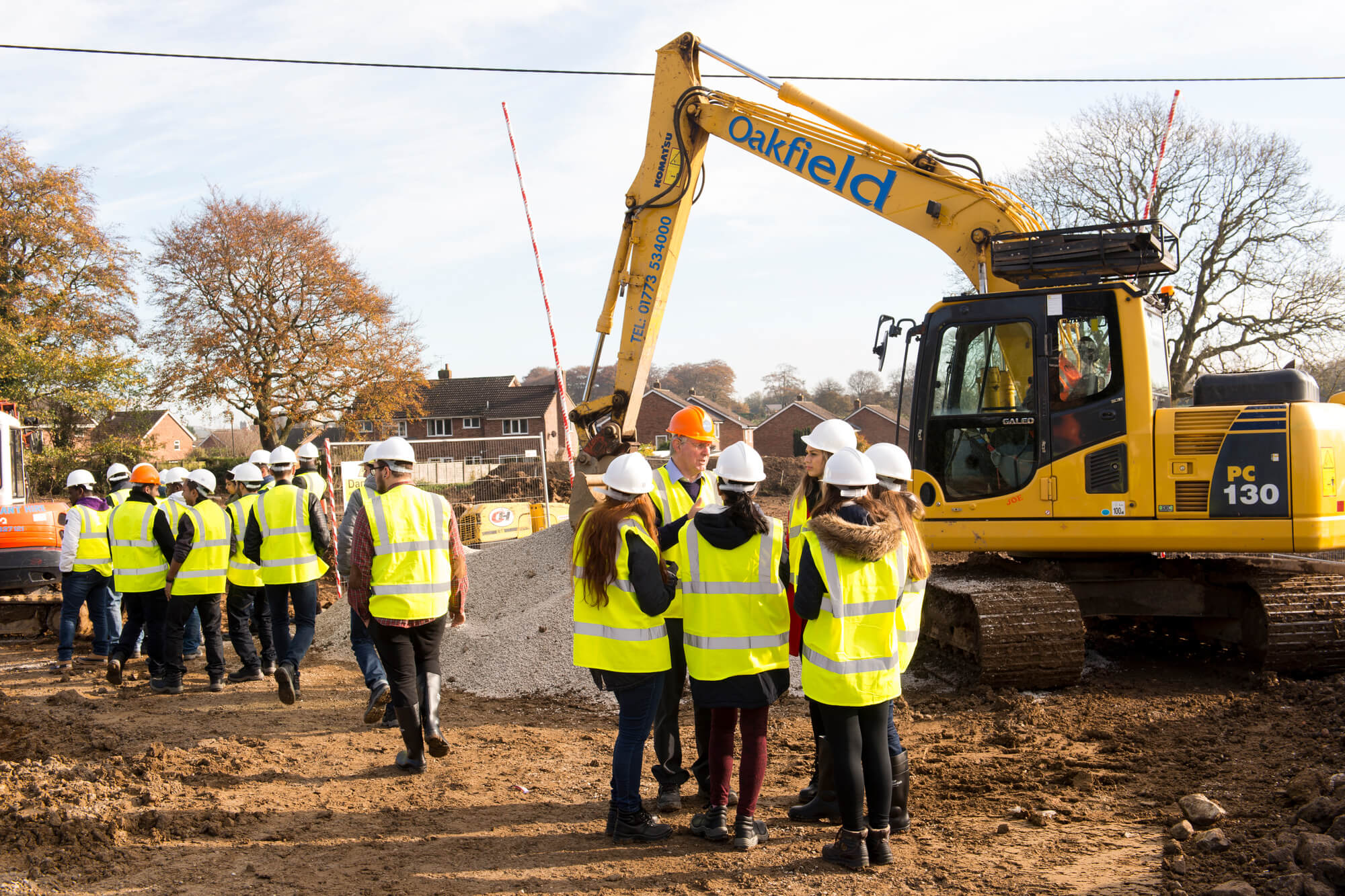 A group of students and lecturer on a construction site on a field trip