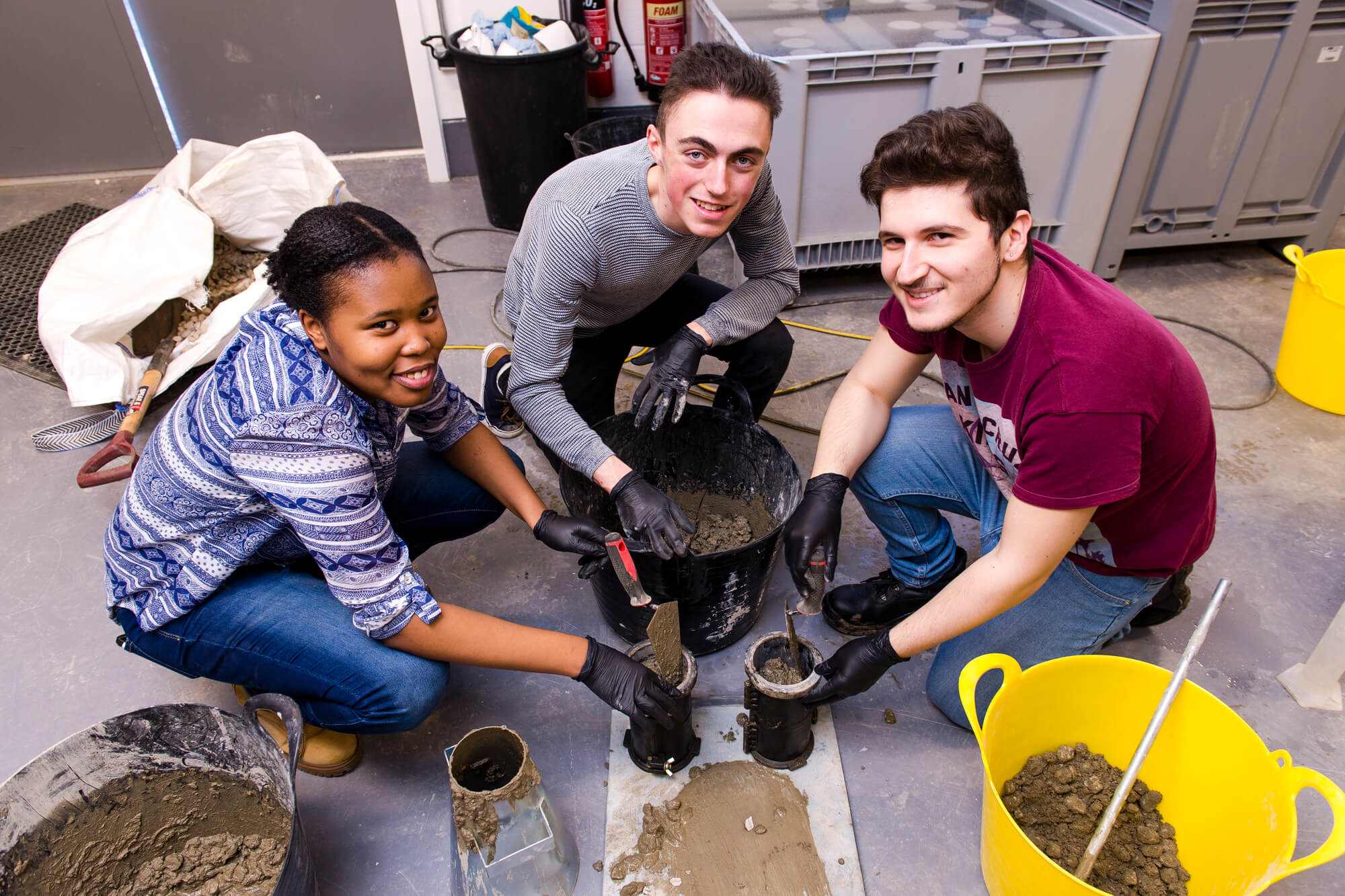 A group of students in the concrete testing lab