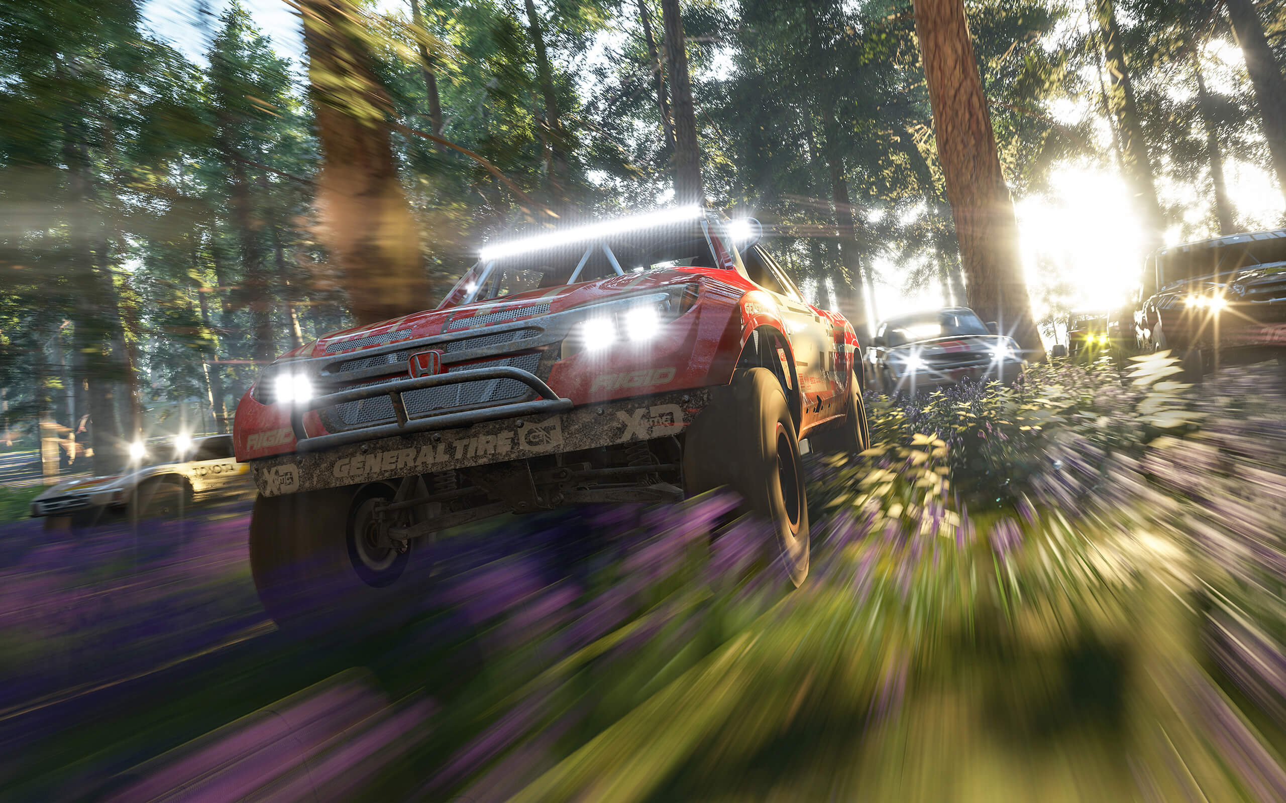Cars racing through a forest from Forza Horizon 4
