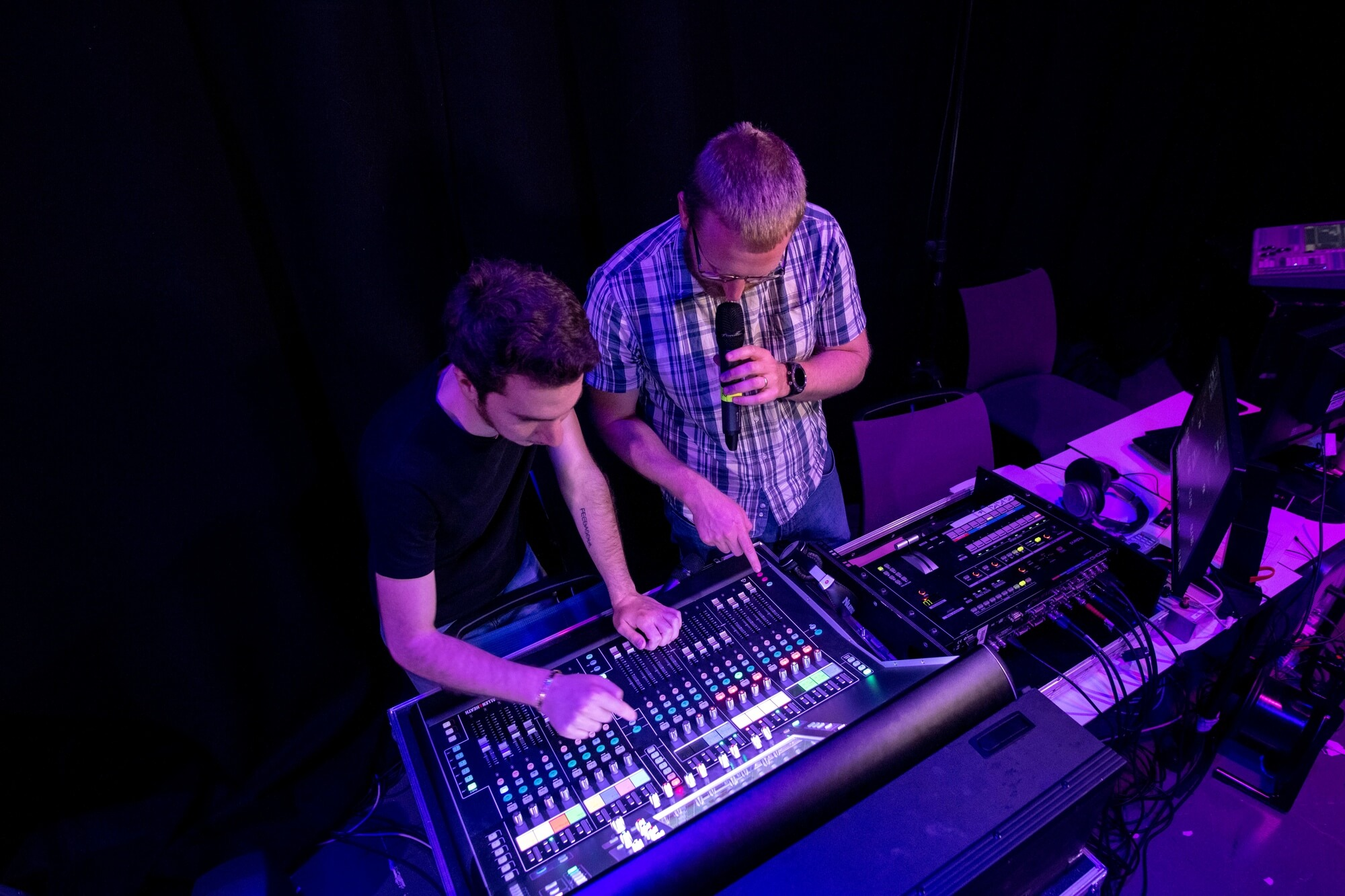 An academic and a student working on a sound desk.