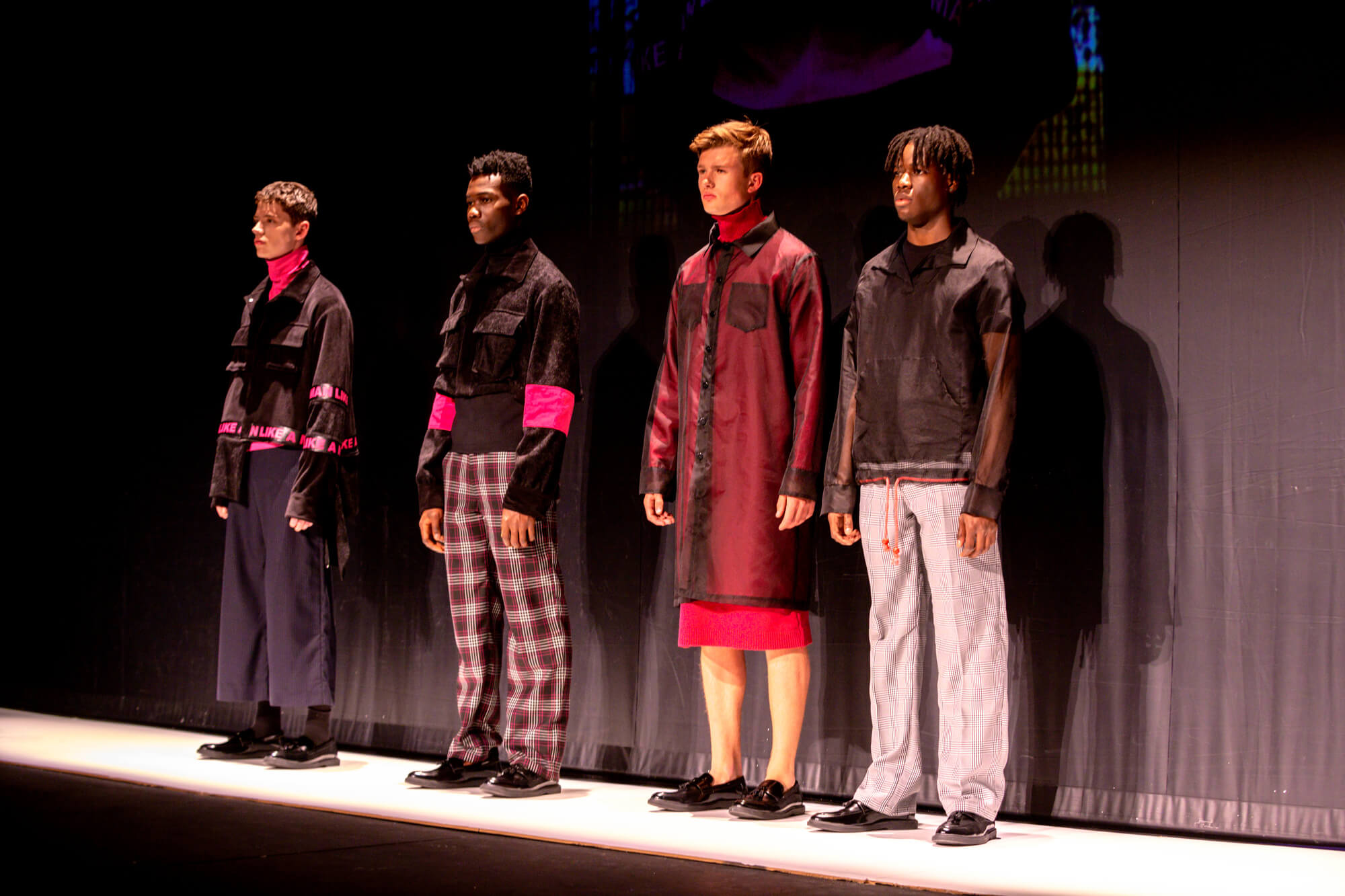 Male models showcase menswear in a catwalk lineup