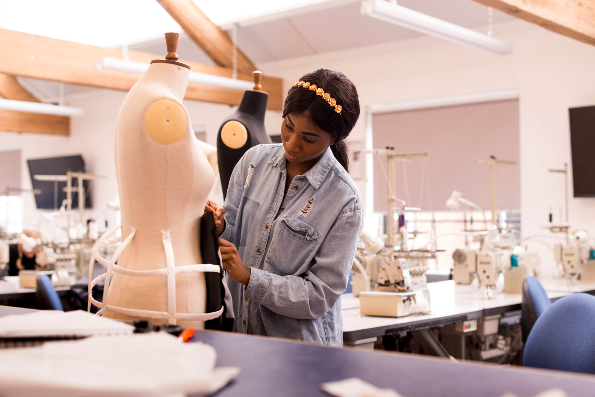 A female pins her clothing design to a mannequin