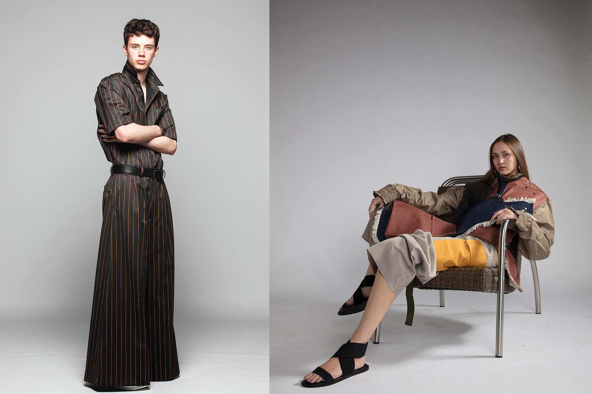 A male stands with their arms folded and a female reclines in a chair for a fashion shoot