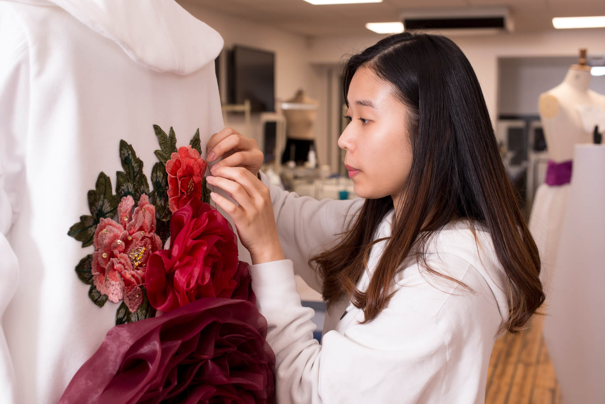 A female puts the finishing touches to a white garment embellished with pink and red floral embroidery and 3d flowers