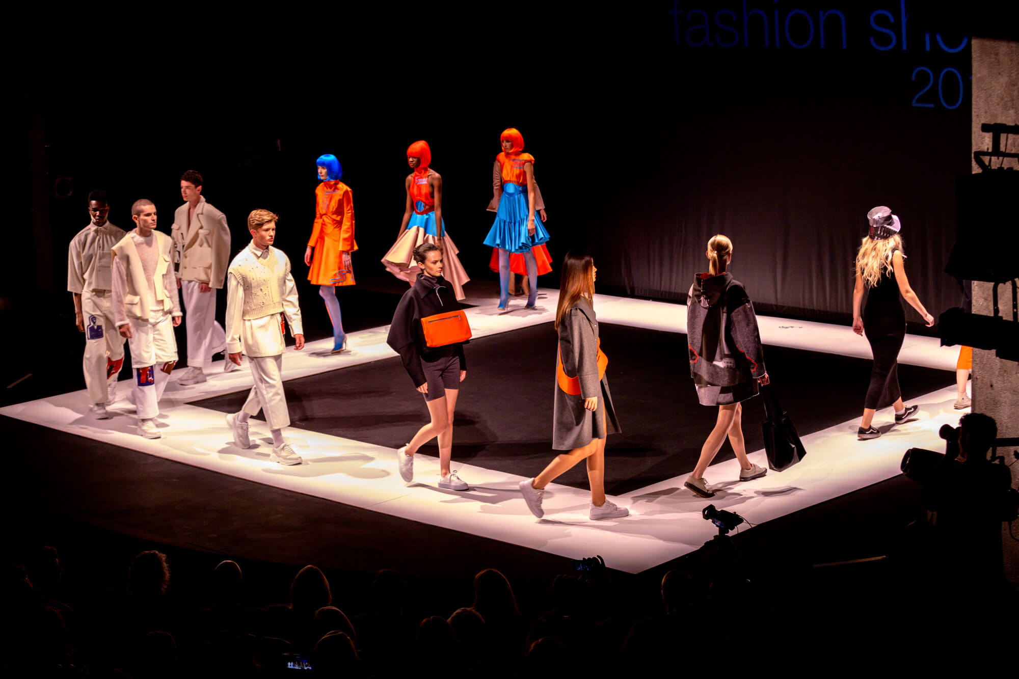 Male and female models showcase clothing designs on a catwalk