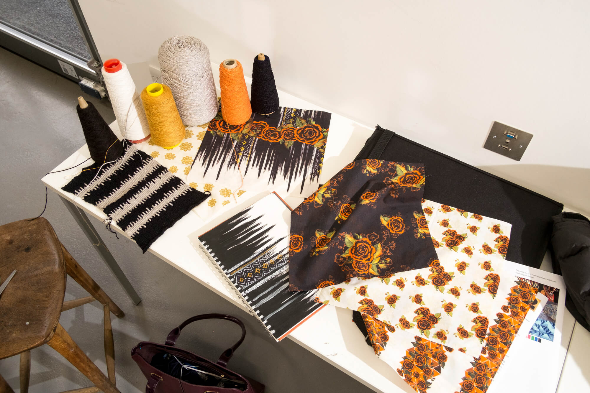 A collection of black, orange and white floral patterned textile samples and yarn on a table