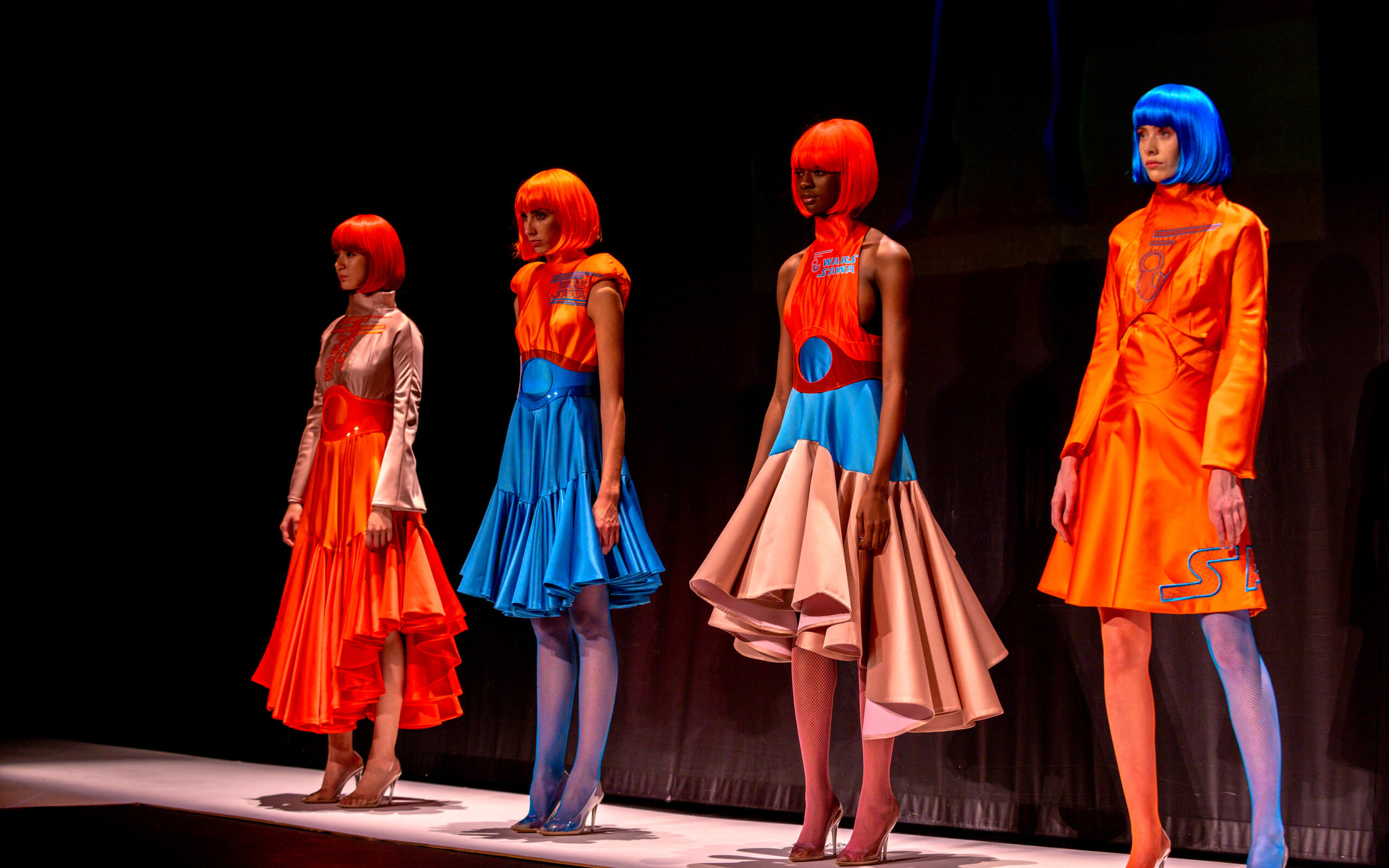 A group of models showcase neon futuristic womenswear on the catwalk