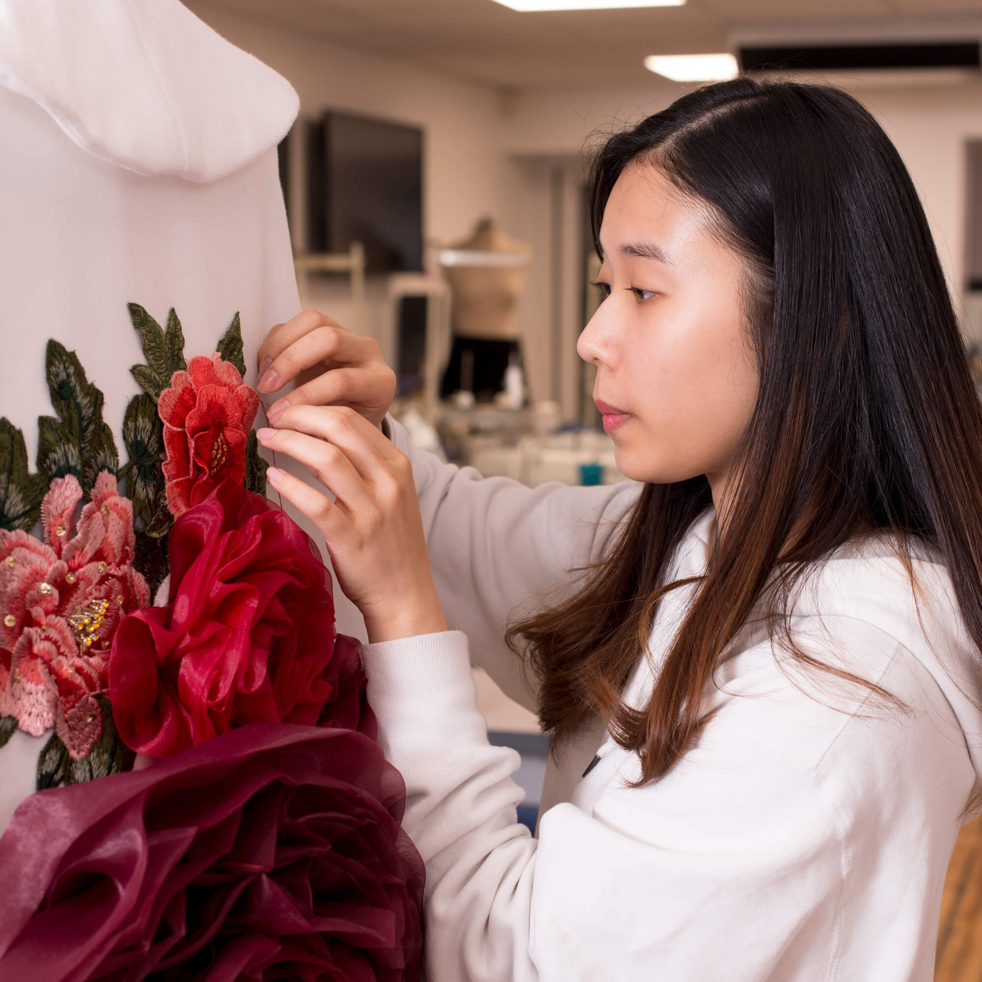 A female touches a white garment embellished with pink and red floral embroidery and 3d flowers