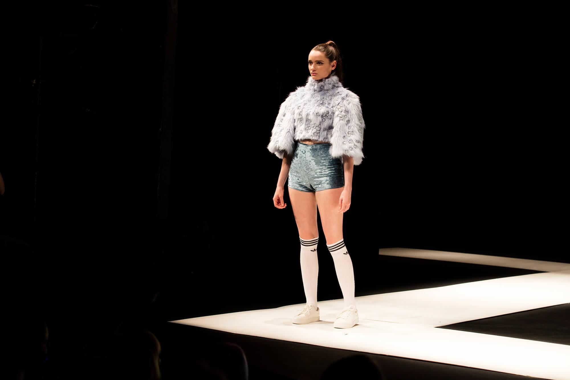 A female models sports socks, a furry jumper and velvet shorts on a catwalk