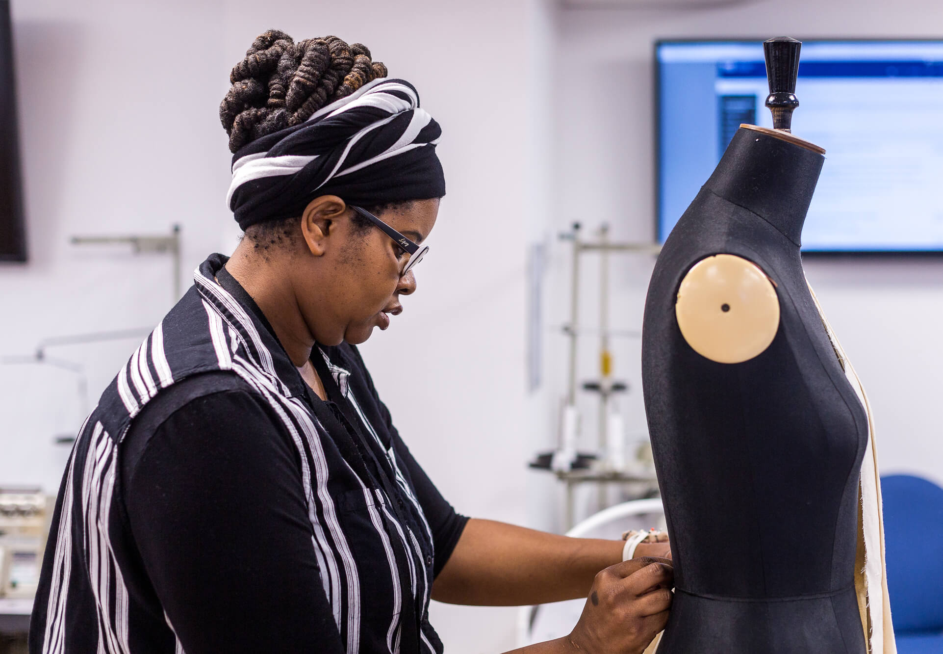 A female pins material to a mannequin