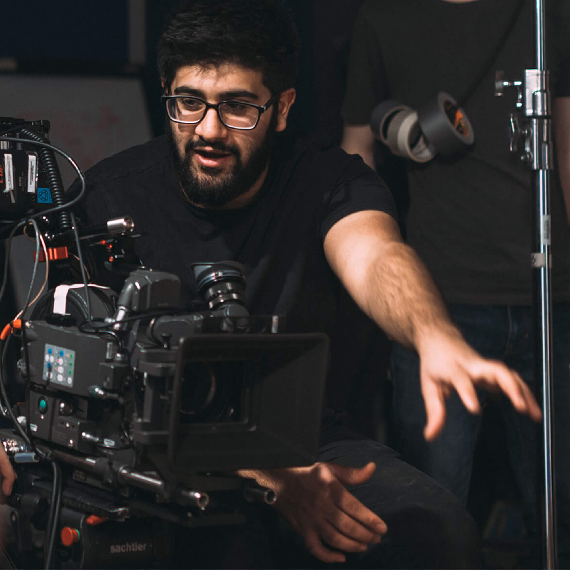 A male directs crew and camera equipment