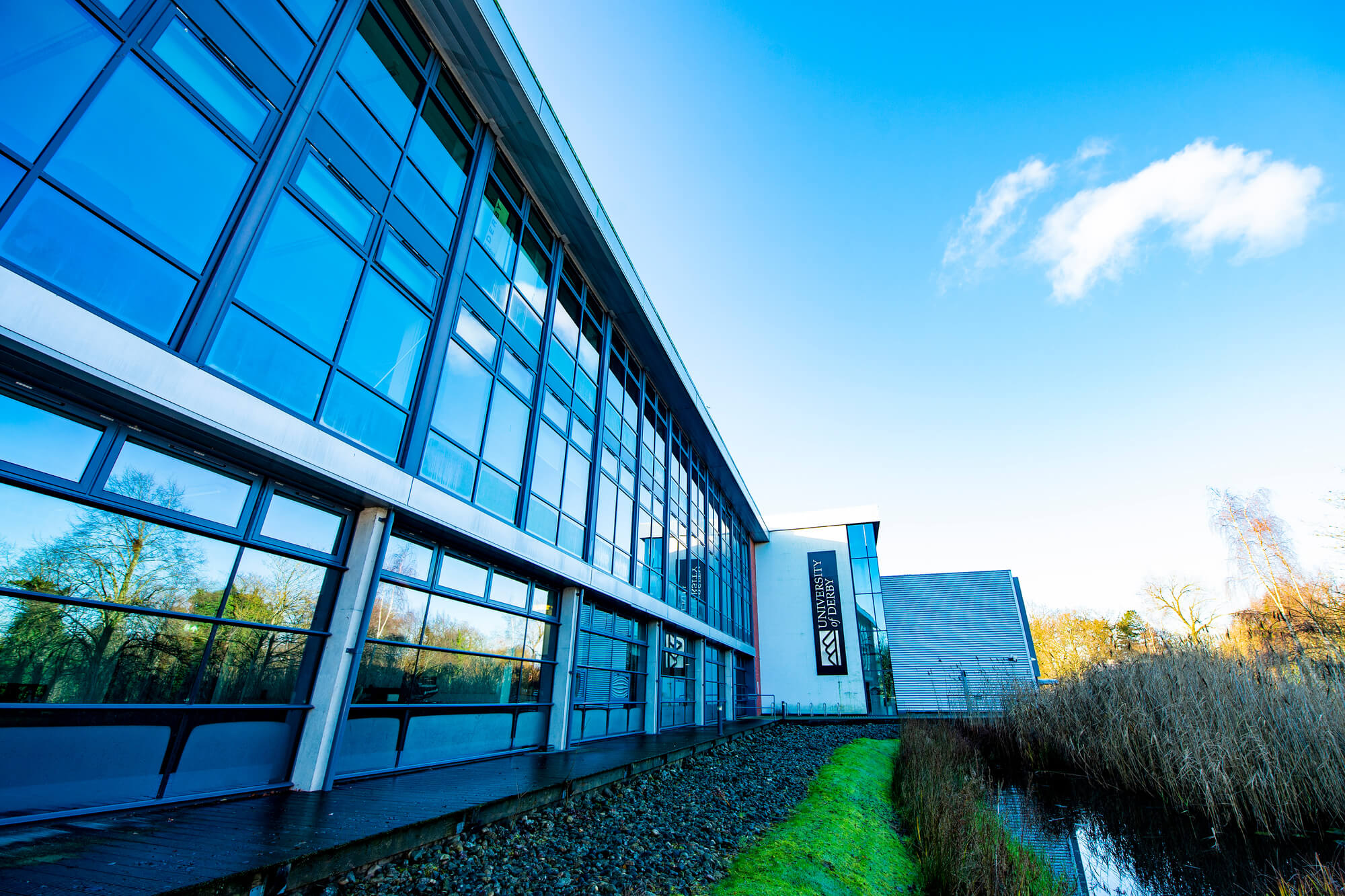 A modern glass fronted building with a brook and grass in front of it and blue sky background