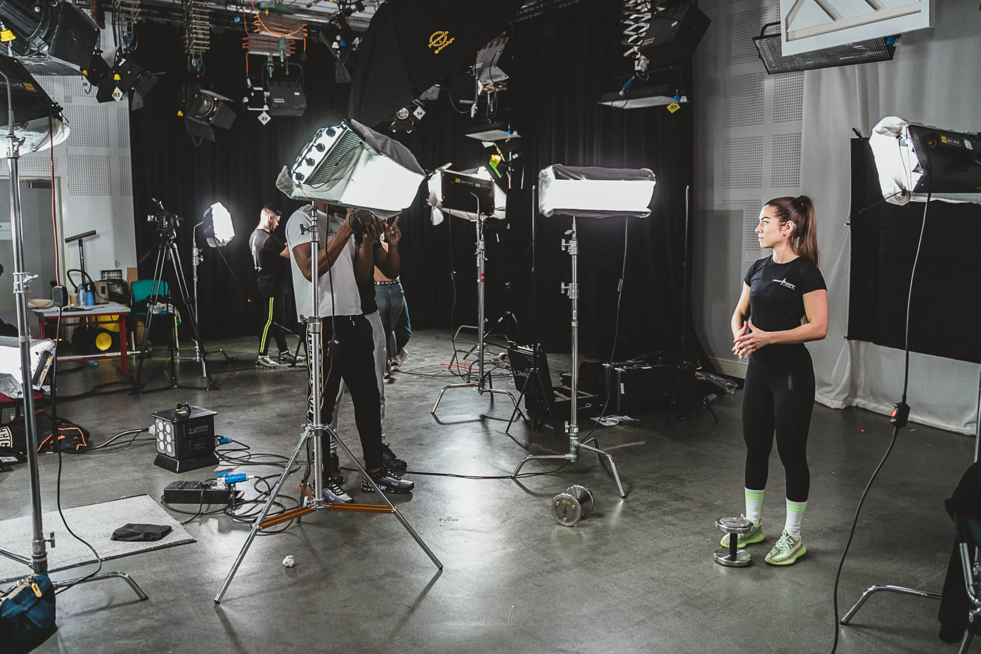 A female models branded gym wear whilst standing by a weight with lights and cameras set up around her in a studio