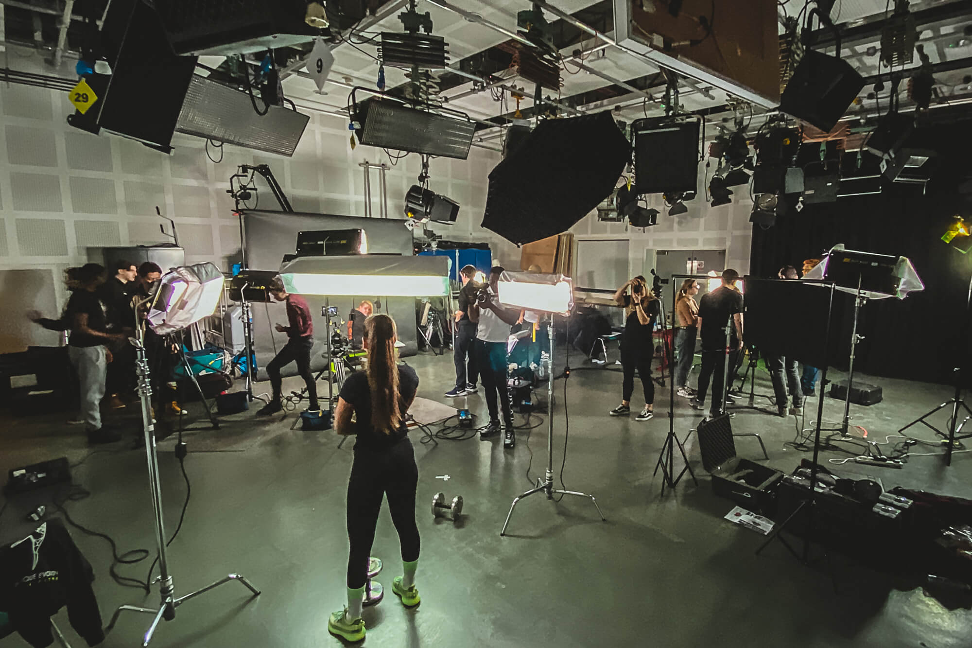 Models and camera operators fill a busy camera and lighting studio