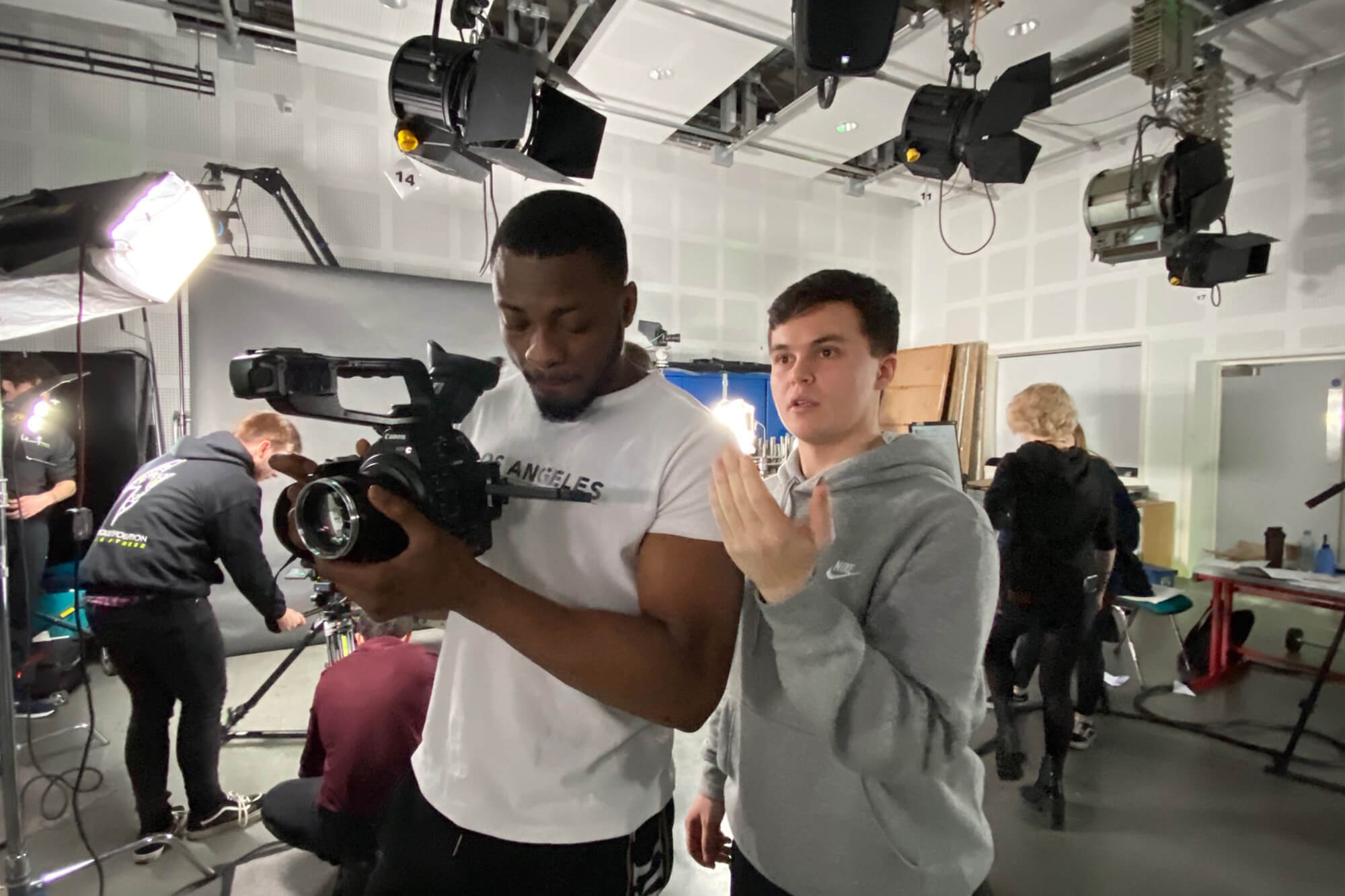 Two male students stand in a camera studio while one holds a camera