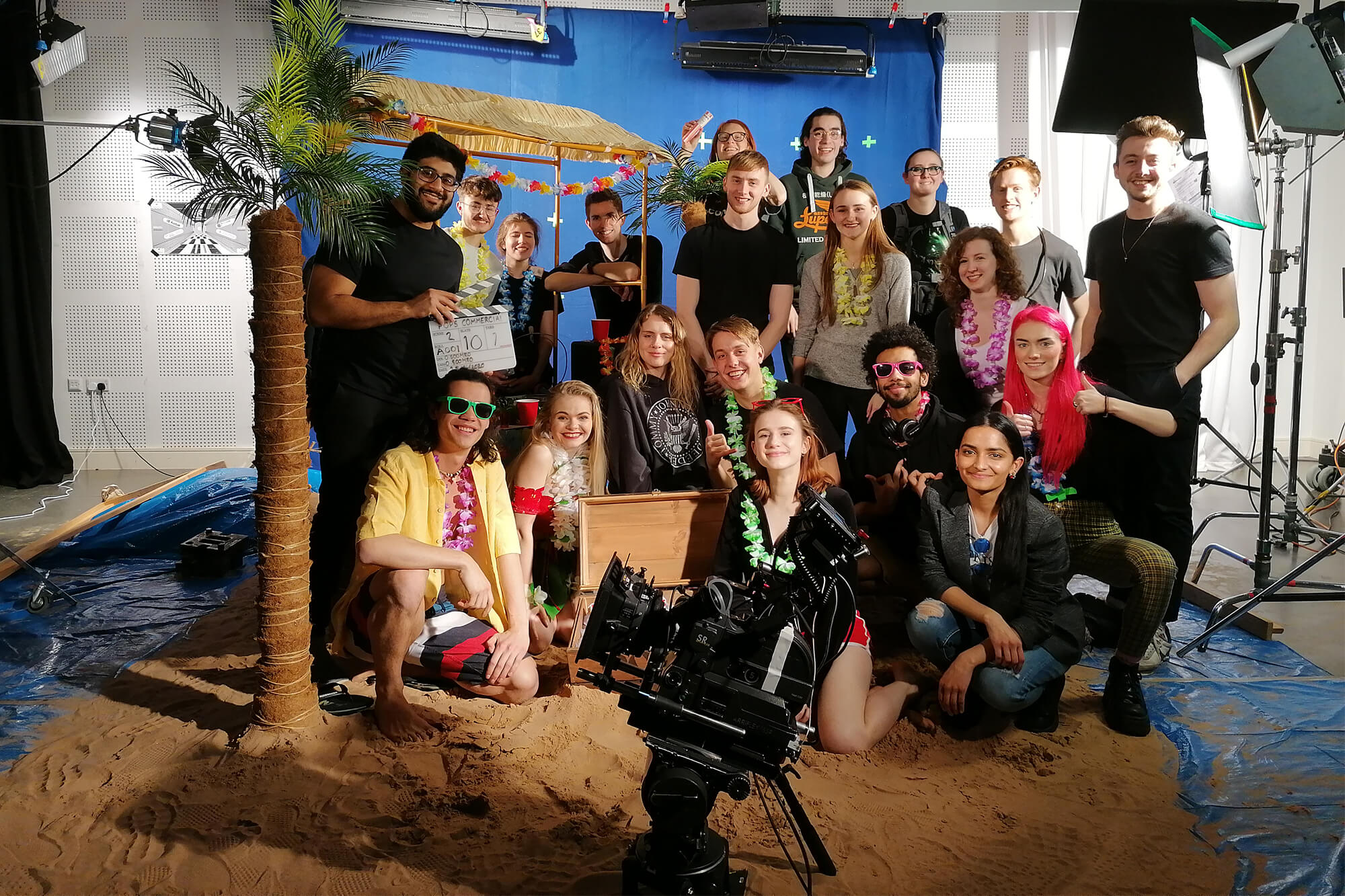 A group of actors and film crew pose for a group photo in a studio location of sand and palm trees