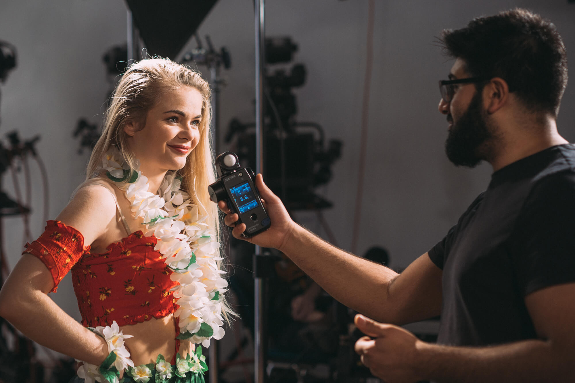 A female dressed in Hawaiian attire goes through final checks with a director before a shoot begins