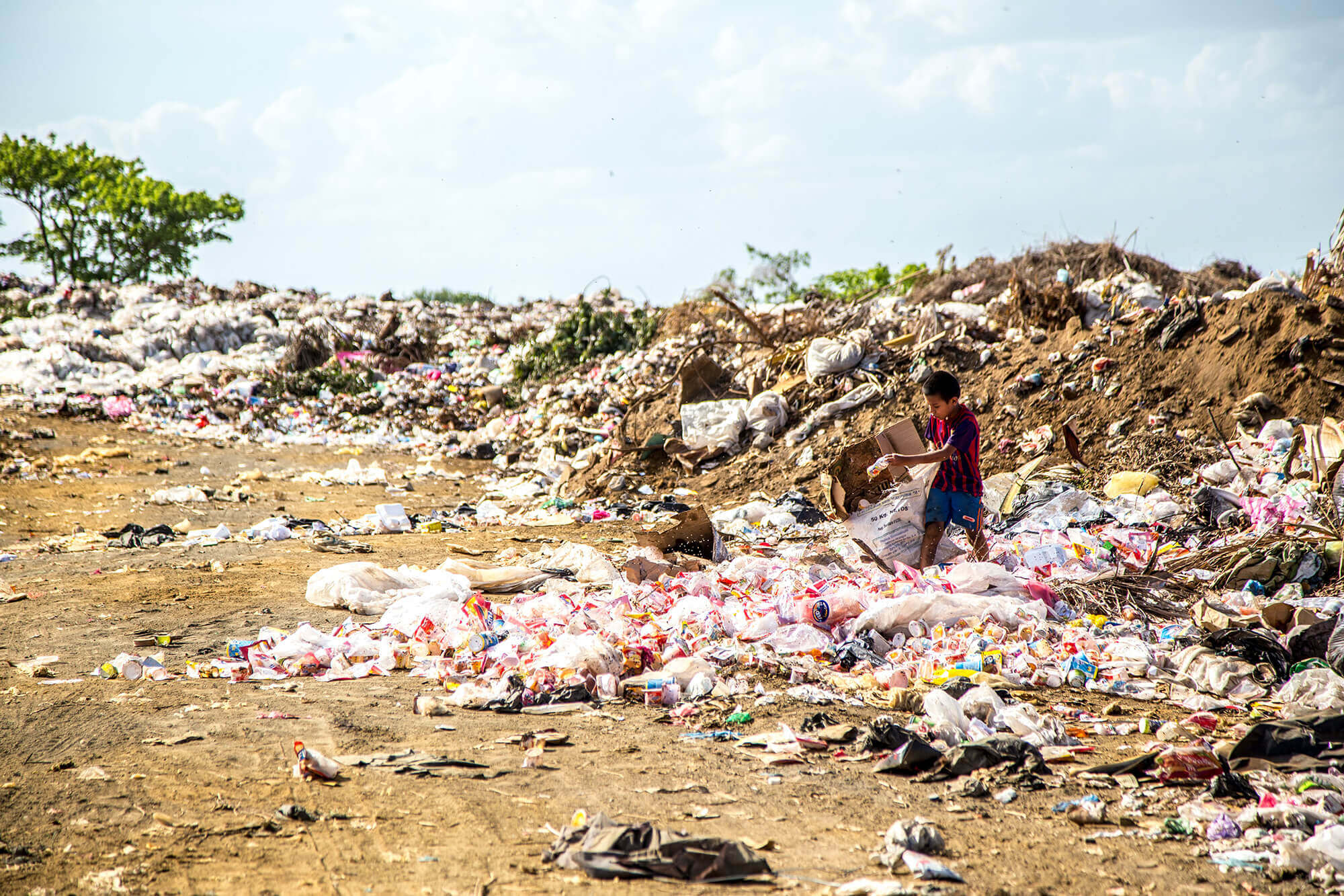 A young child walking through a waste plant