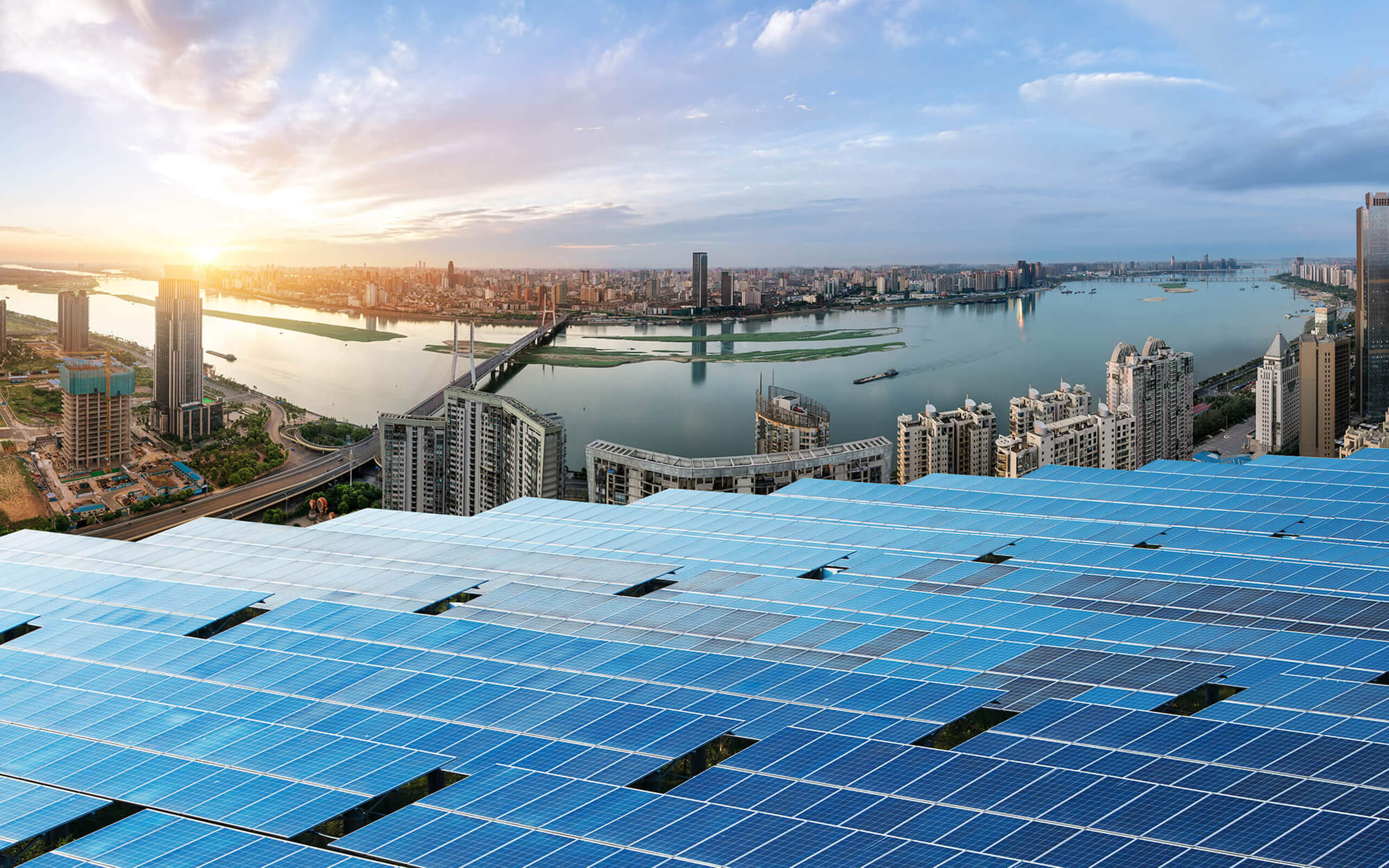 Solar panels in focus with a large city in view behind