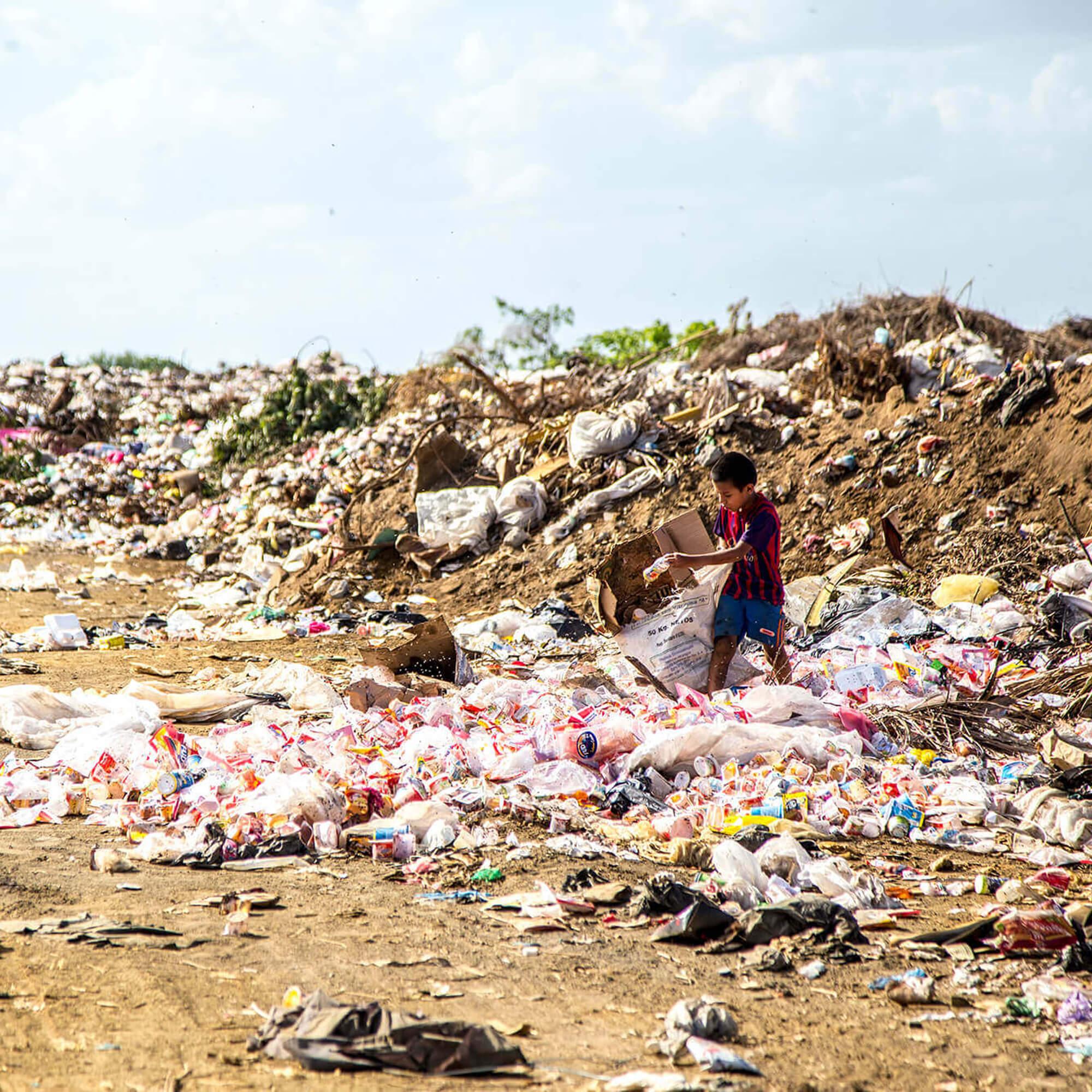 A young boy climbing through a pile of litter.