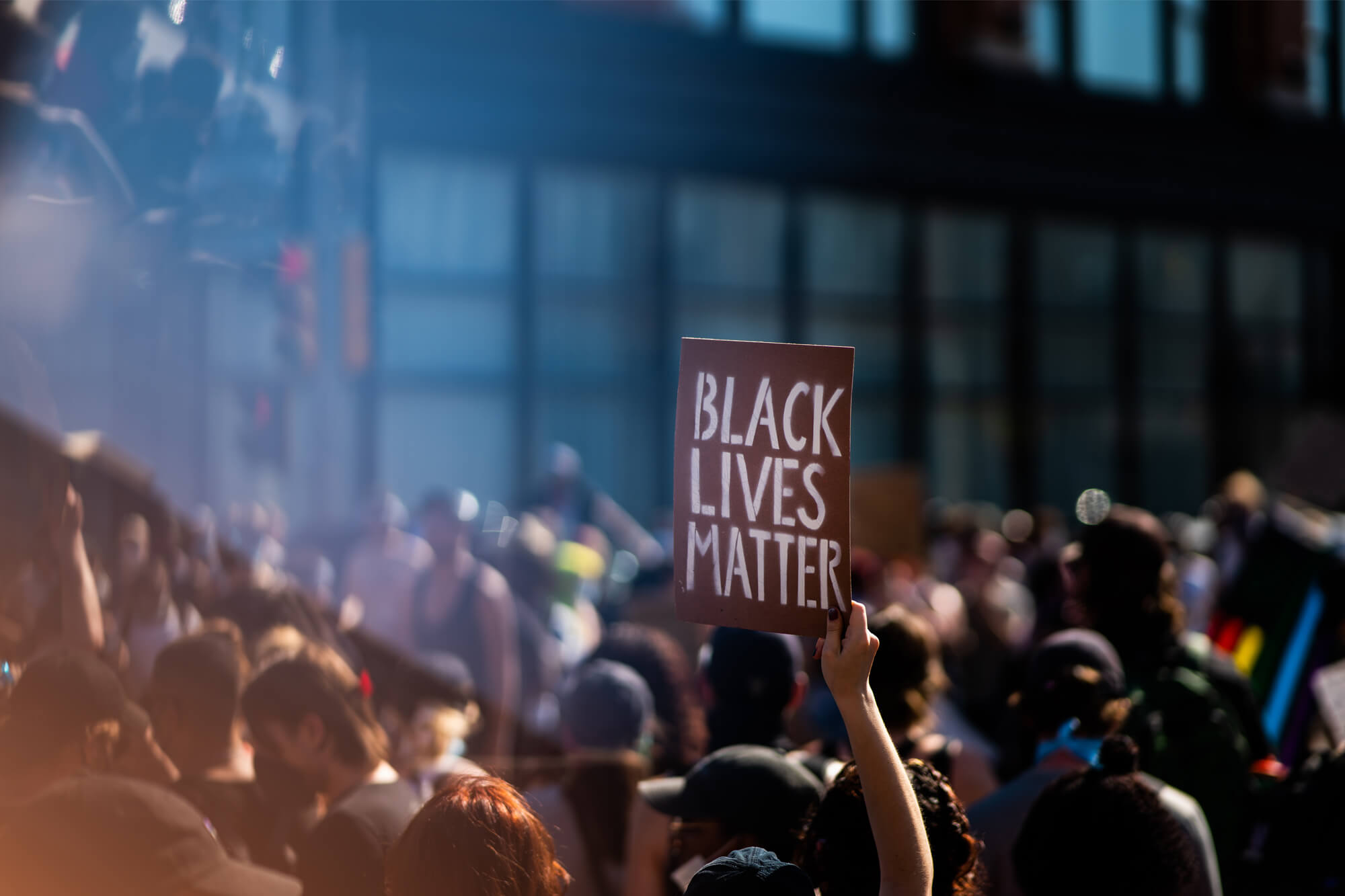 An image of the Black Lives Matter march - people marching, with someone holding up a Black Lives Matter placard.