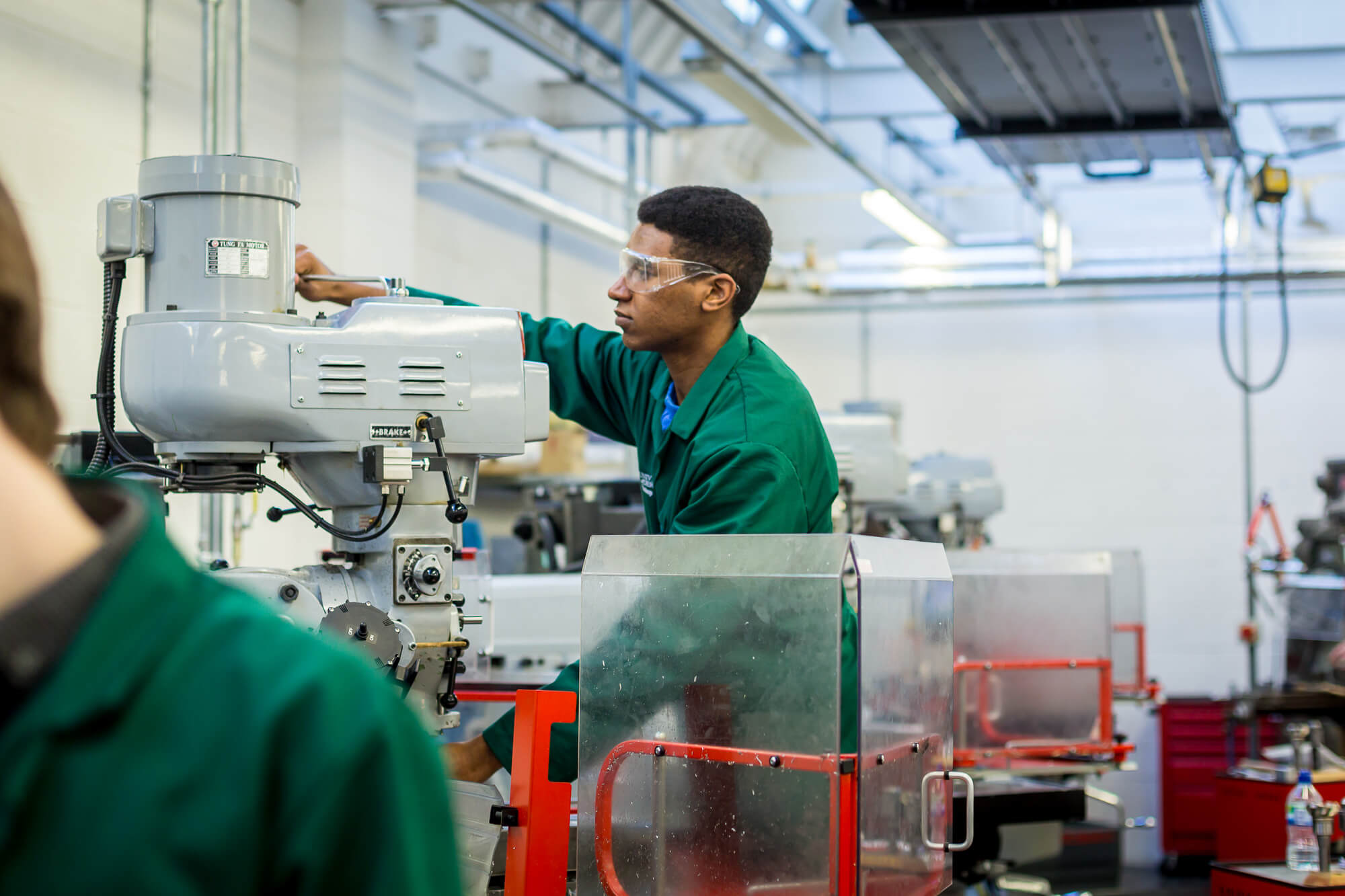 A Mechanical Engineering student using a lathe in the workshop