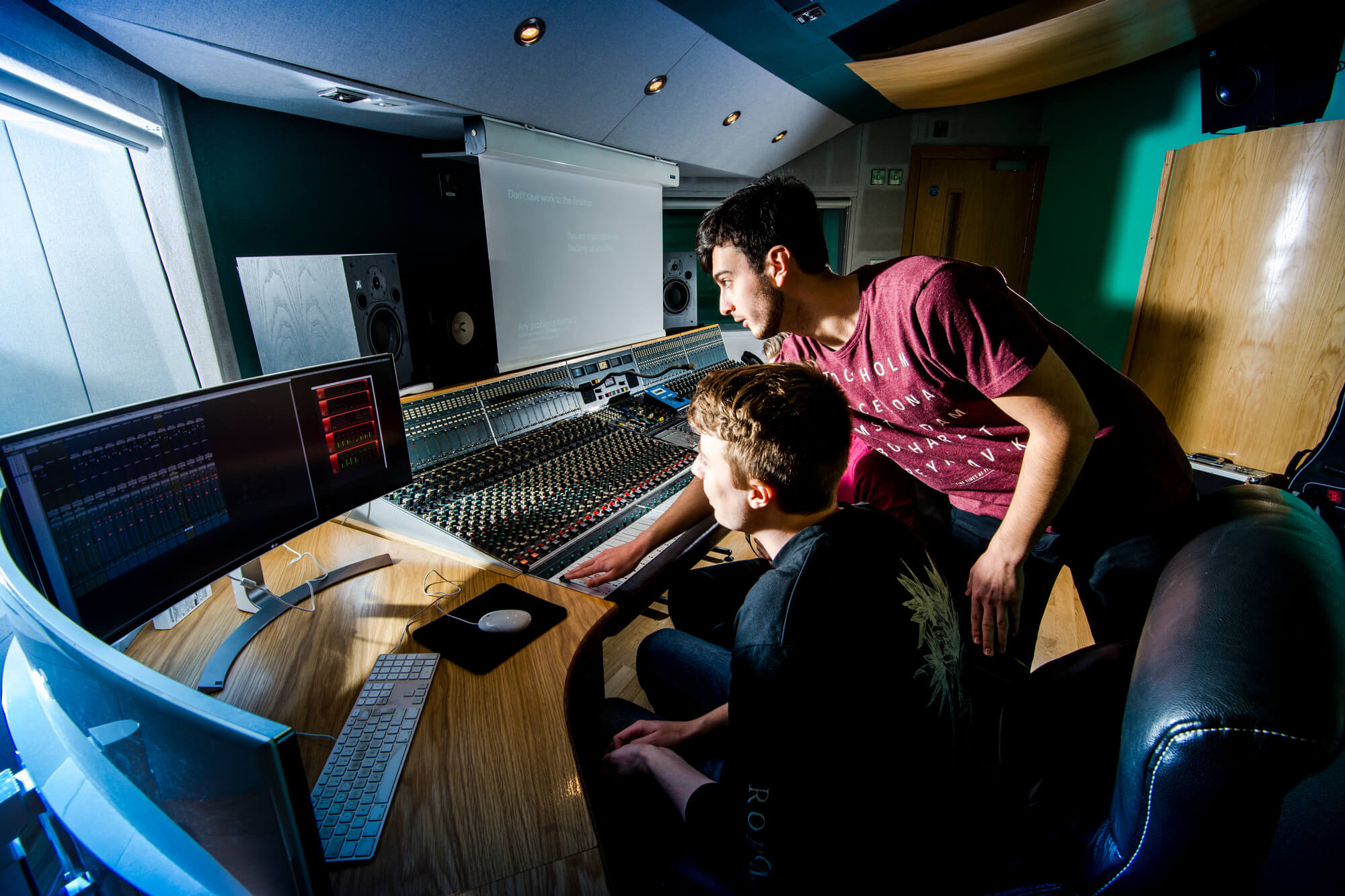 Two males use equipment in a music studio
