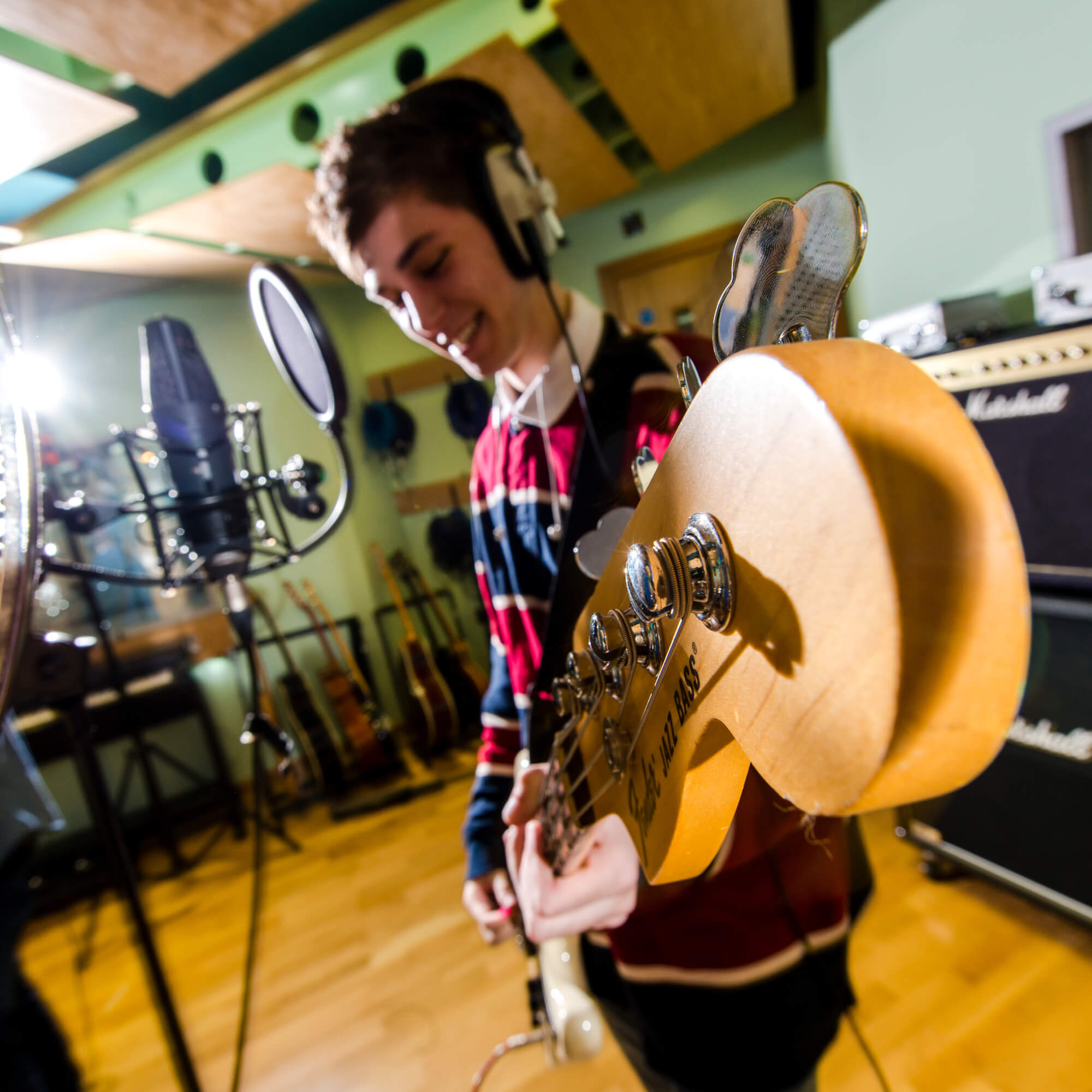 A close up of a man playing guitar in a recording studio
