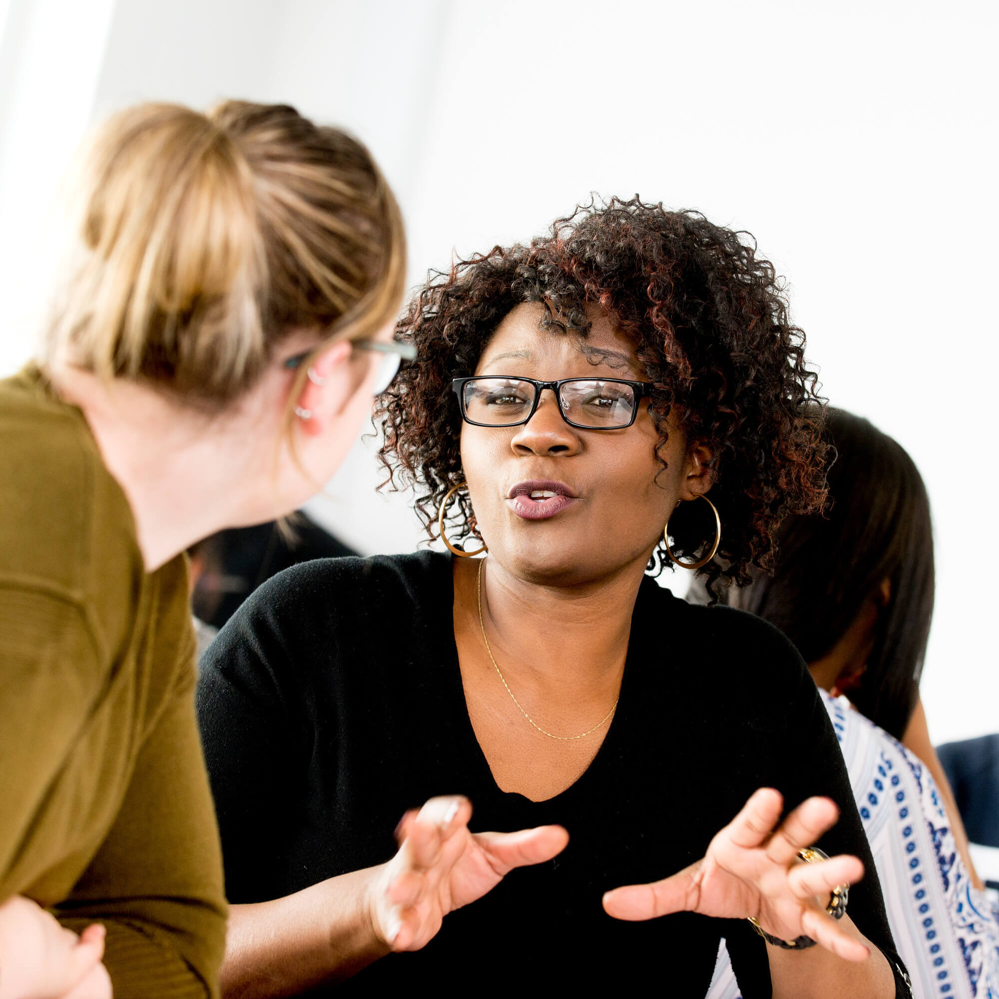 Two women talking in a class room