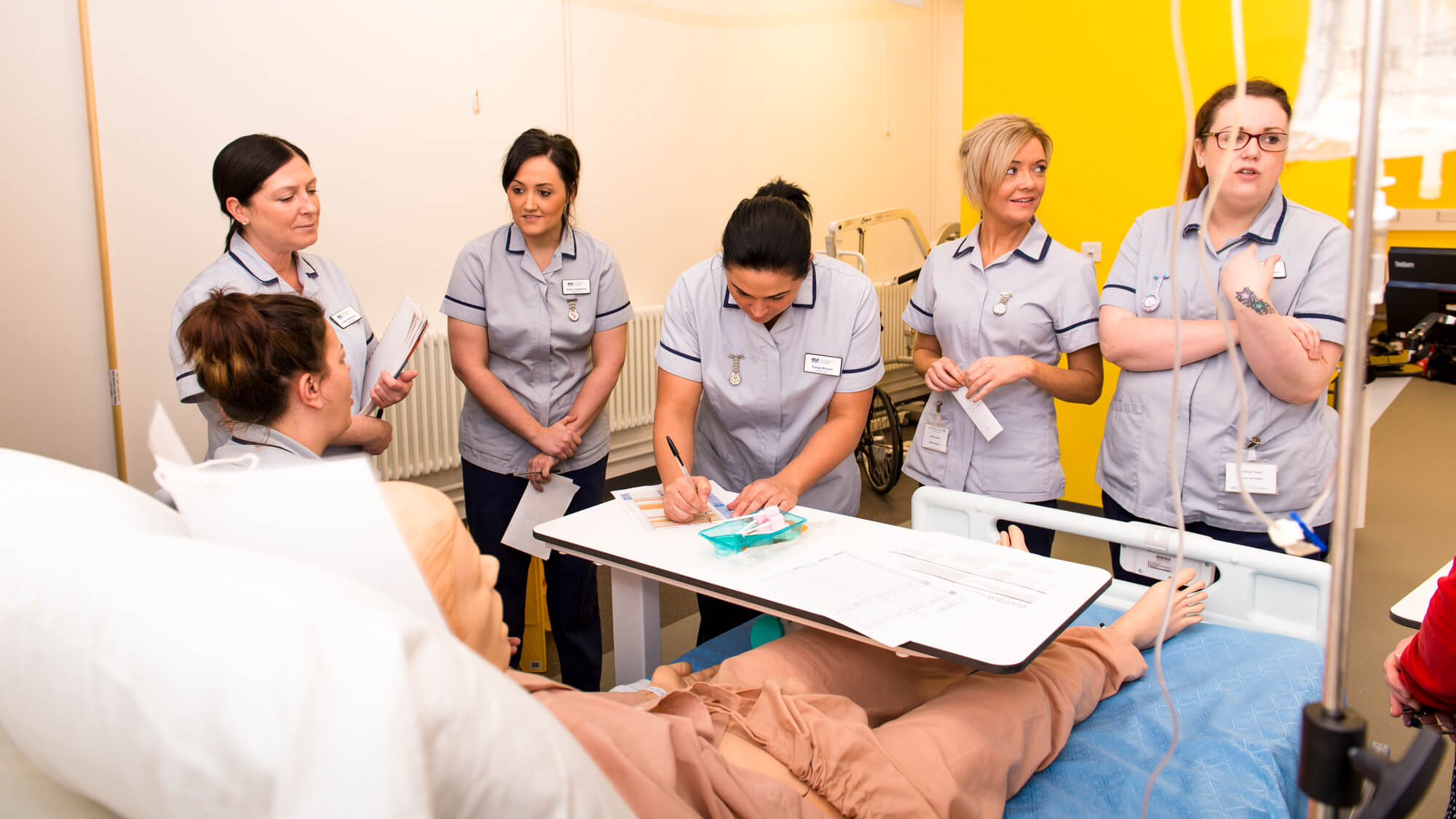 Students in the mock ward standing around a bed looking after an artificial patient