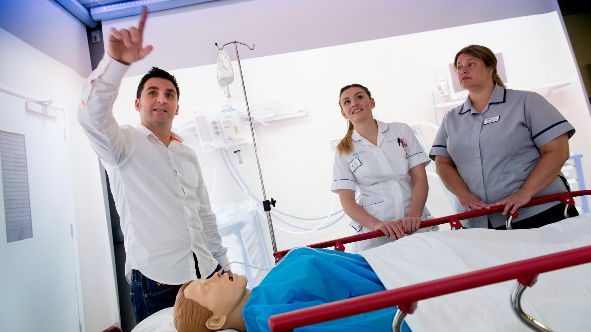 Two students being show the immersive suite in the mock ward at the University of Derby
