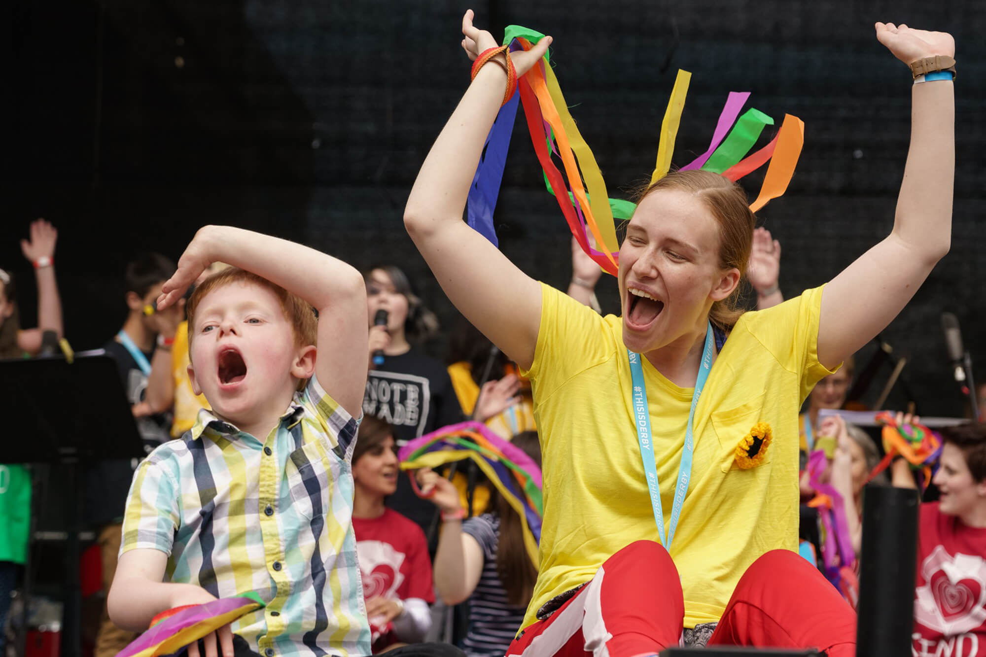 A young boy in a checked shirt raises his arm above his head whilst a lady sitting next to him in a bright yellow t shirt raises her arms that are holding ribbon streamers as she cheers