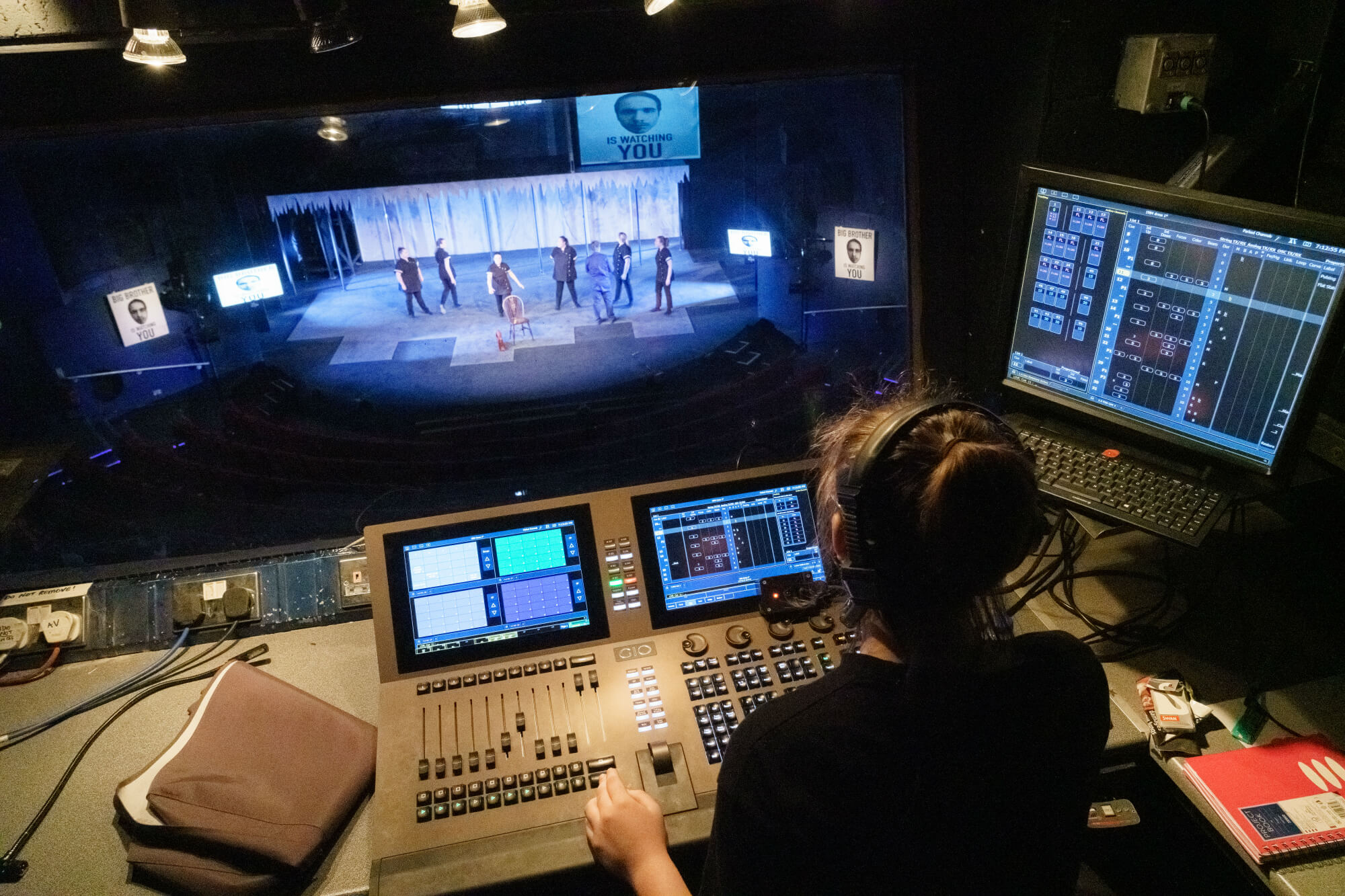 A view over the shoulder of a student at the sound and light controls of a theatre stage