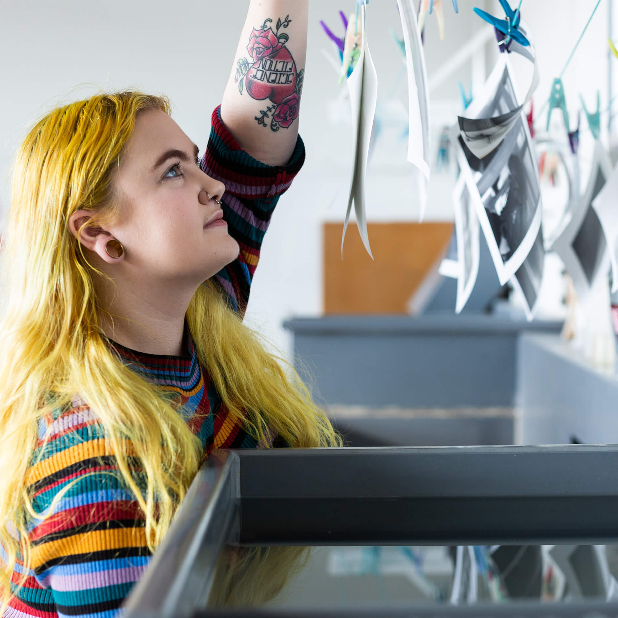 A female student hangs photos in a lab