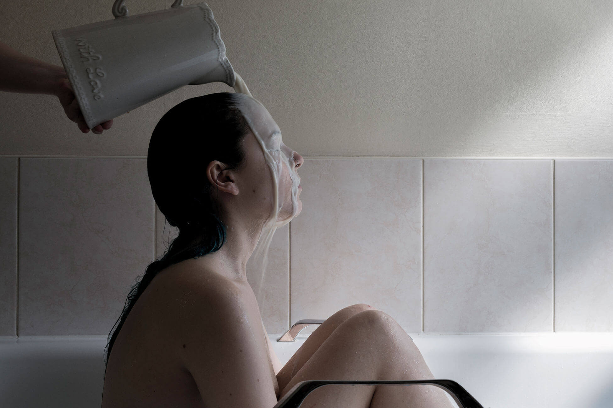A woman in a bath having milk poured over her