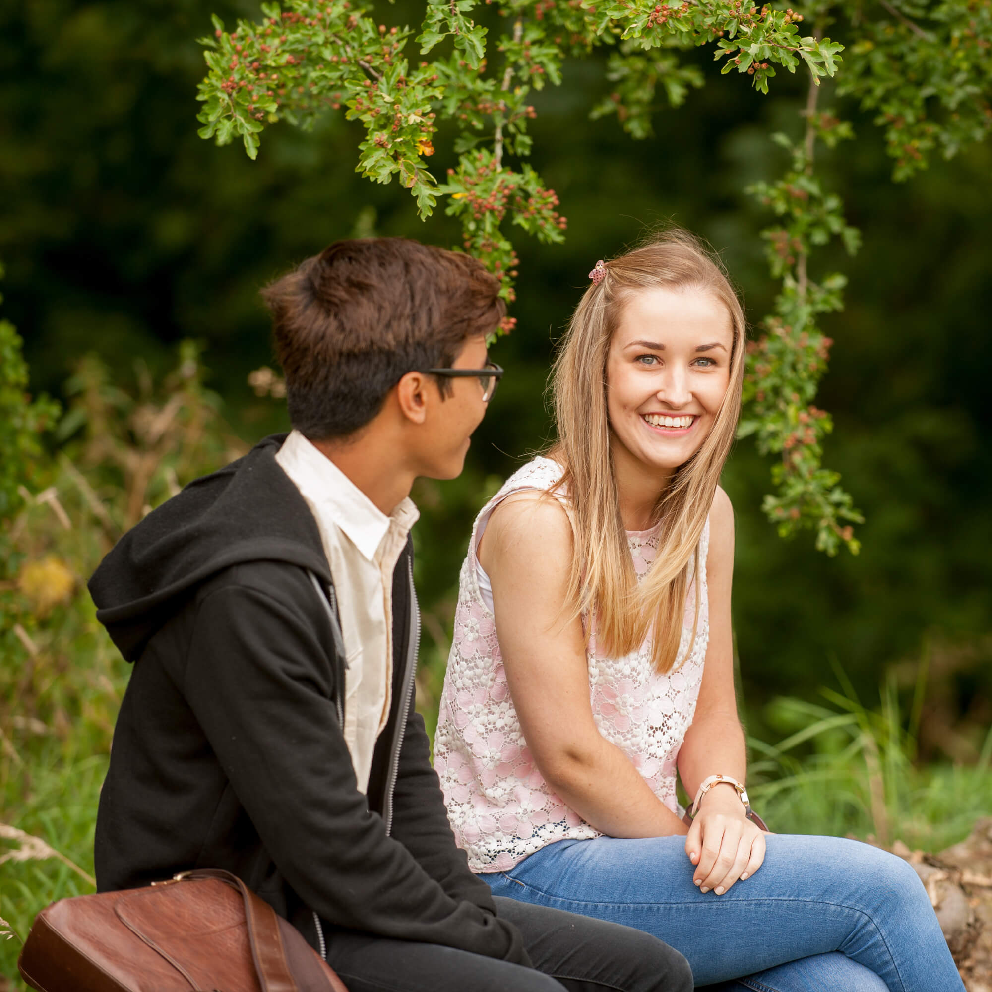 Boy and girl sitting in the park on a bench talking