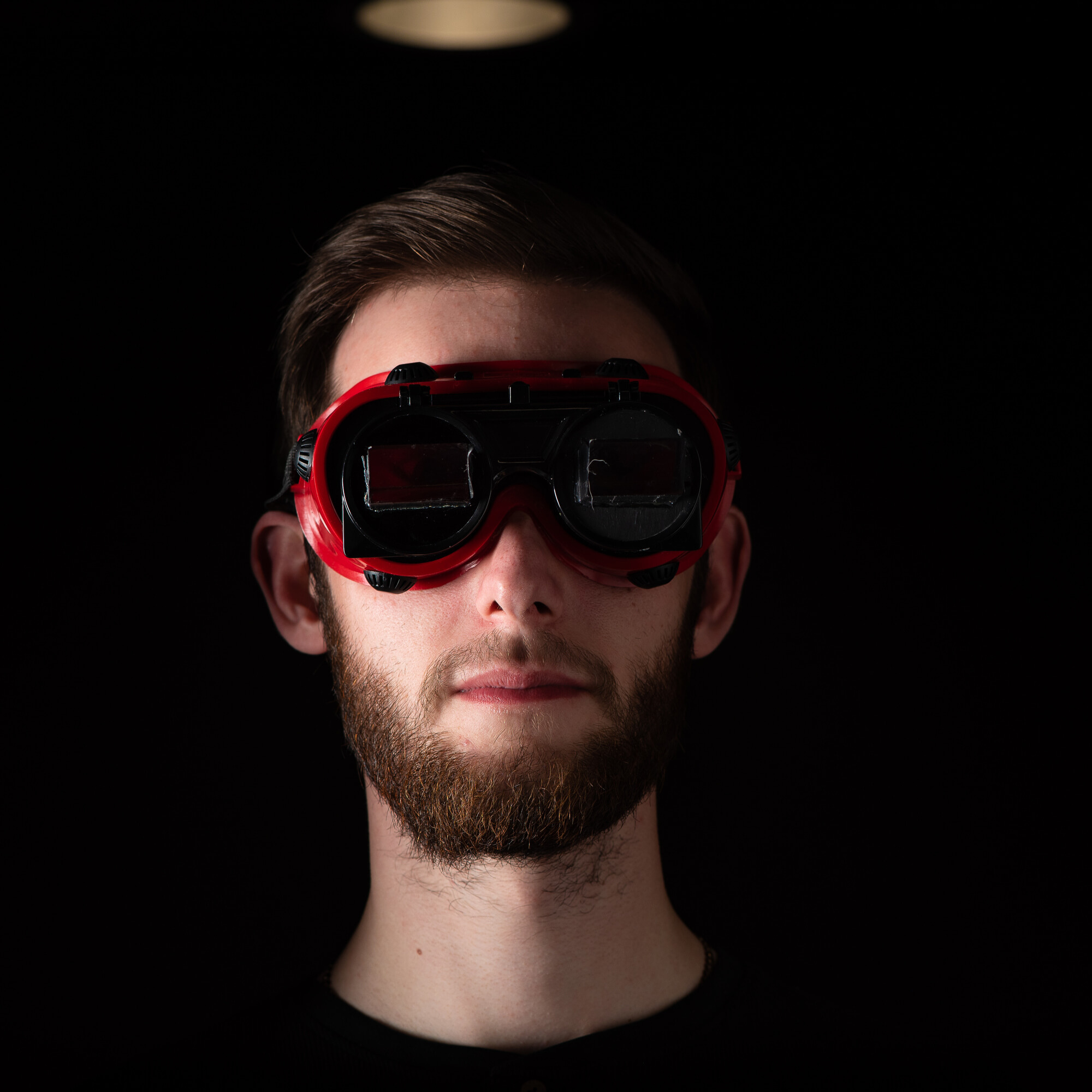 Male wearing red goggles in black room
