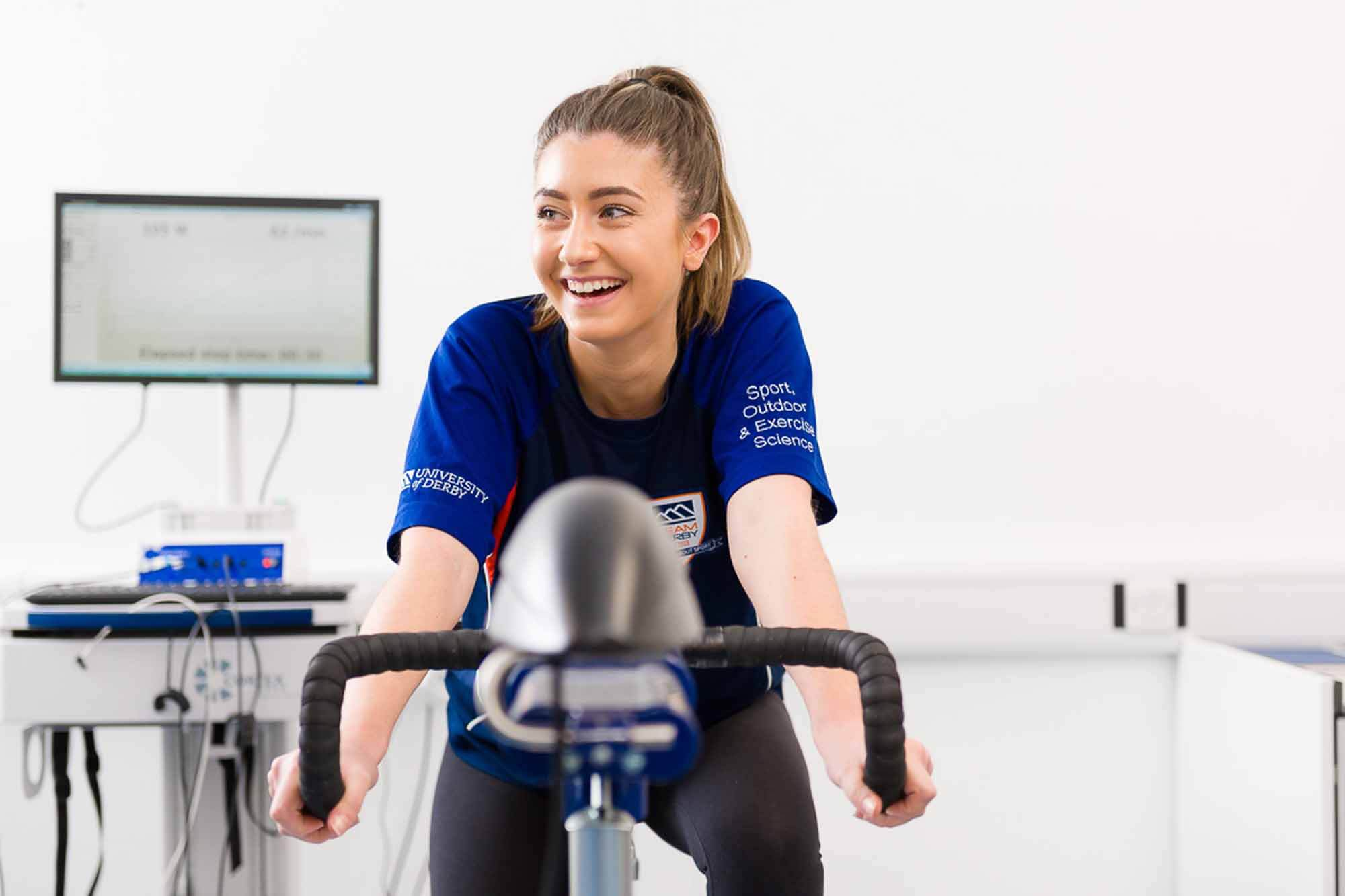A female student sitting on a bike in the Human Performance Unit in our Sports Centre.