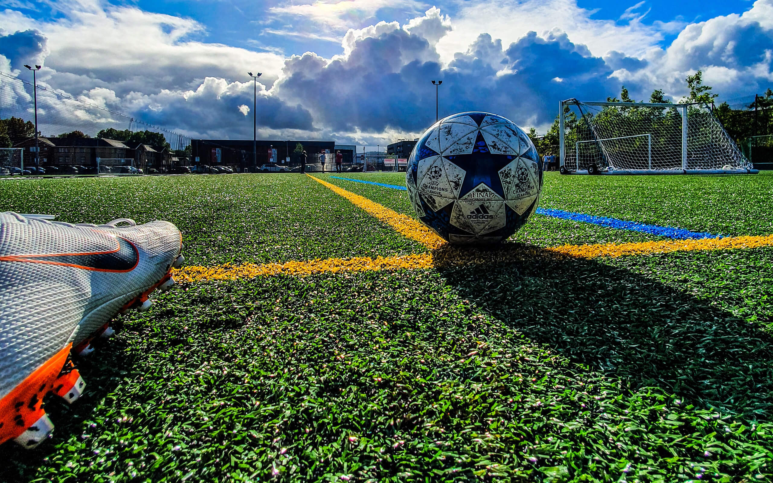 Image of a football boot about to kick a football on a football pitch