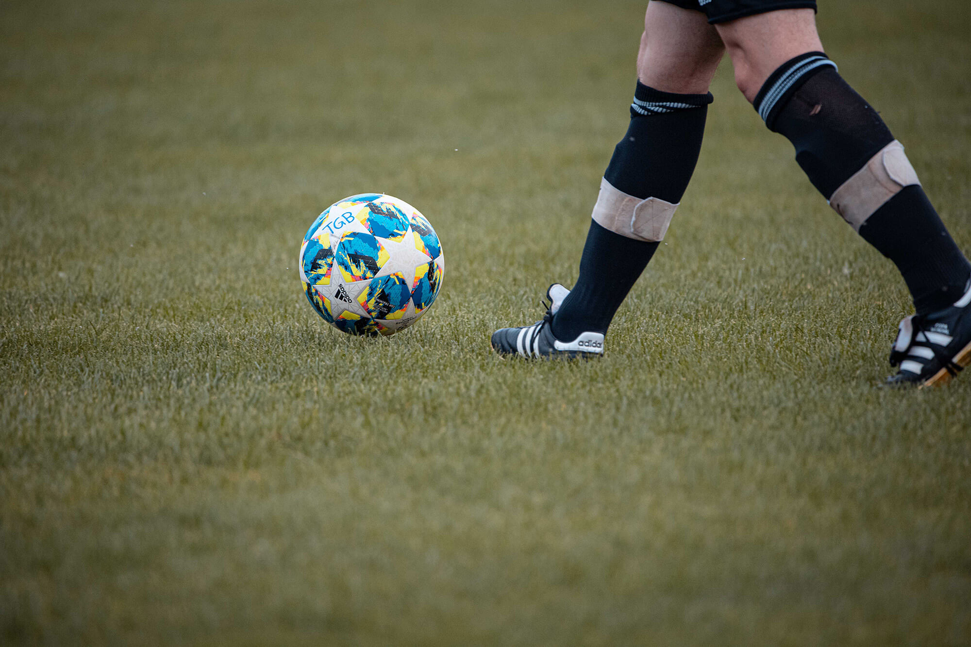 Image of a football being kicked - legs are shwon from the knee down with black football socks and football boots