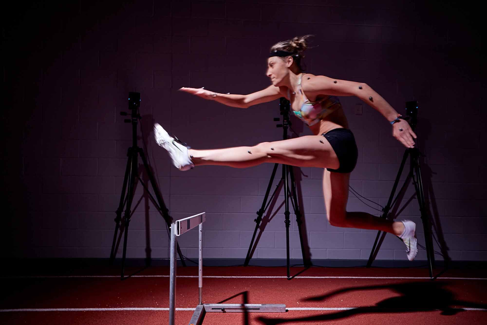 A female jumping over a hurdle